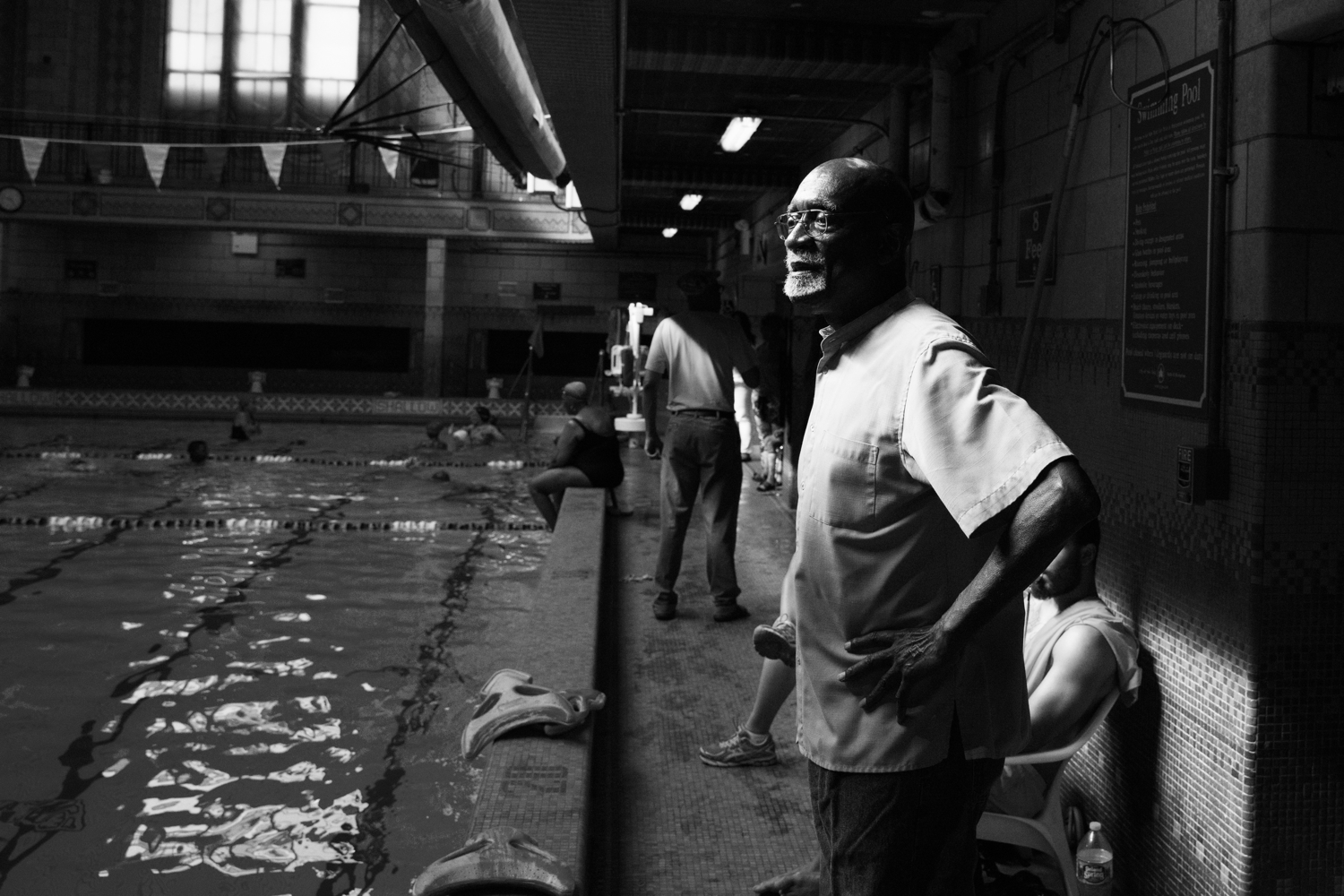 "Luther Gales looks out at his youth team practice at the Hansborough Recreation Center. Gales said, ""Teaching the youth is rewarding, especially seeing a child with no skills become an accomplished swimmer — it's great."""