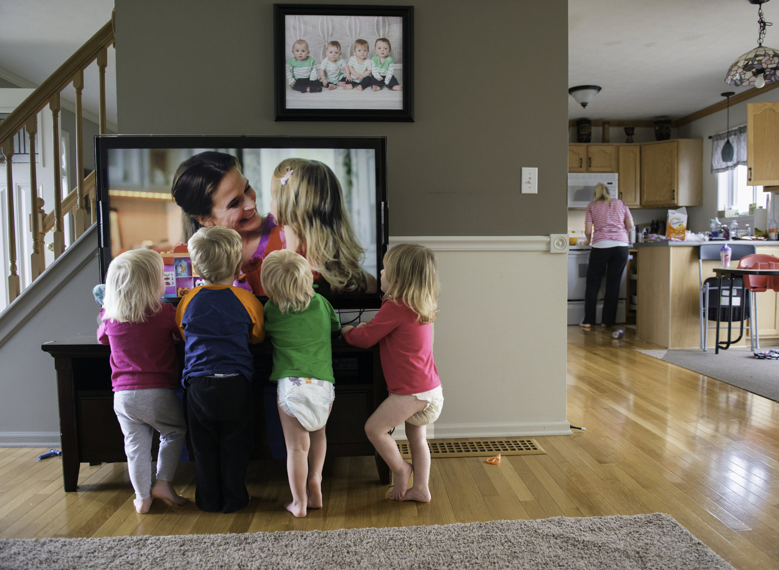 The Larson quadruplets (from left to right) Ashlyn, Brody, Cooper, and Kylie all watch television as their mother Courtney Larson prepares a snack for them in the kitchen on Nov. 16, 2014. Courtney often puts on the television to distract the children while she prepares food or does chores around the house.