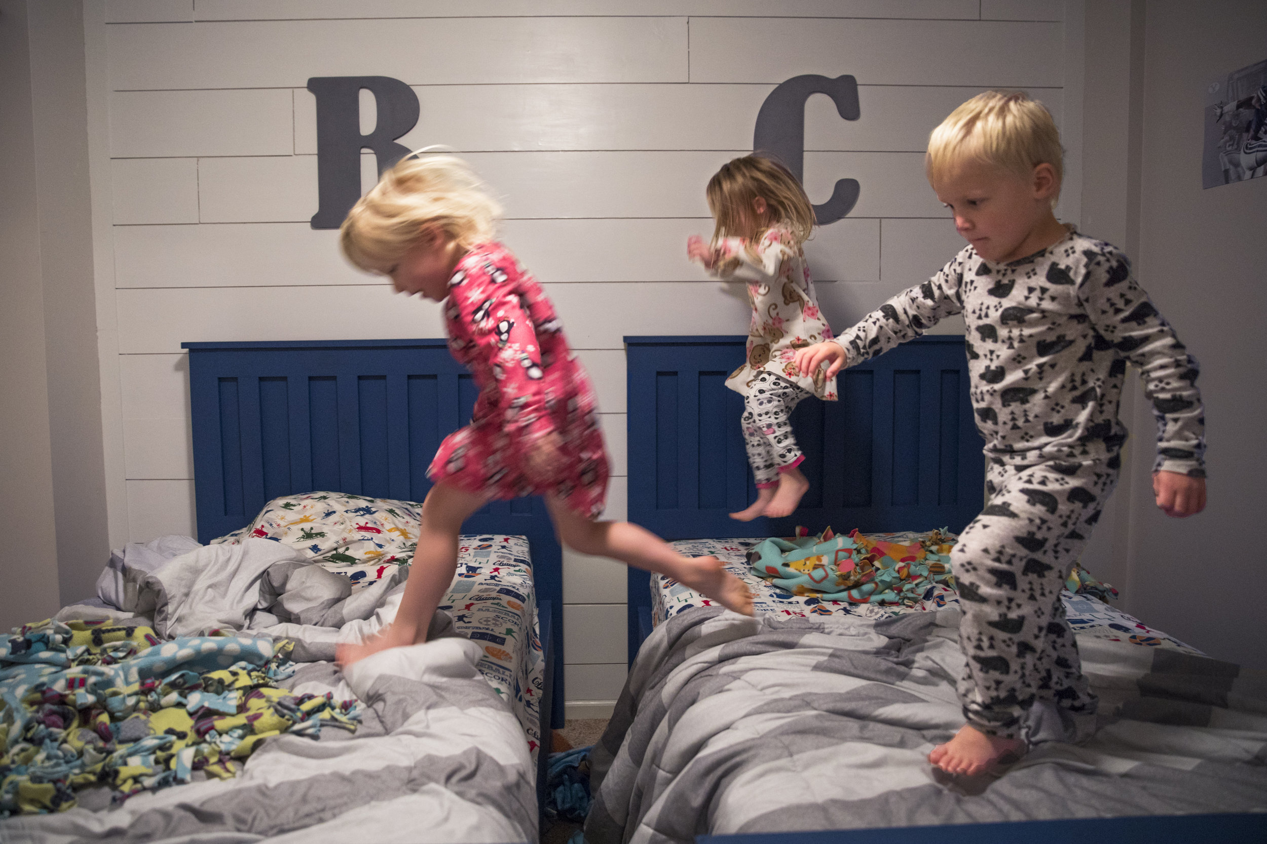 """Ashlyn, Kylie, and Cooper jump on the boys' beds as their mother Courtney sings, """"Five little monkeys jumping on the bed"""" on Oct. 23, 2016 in Lima, New Yo"""