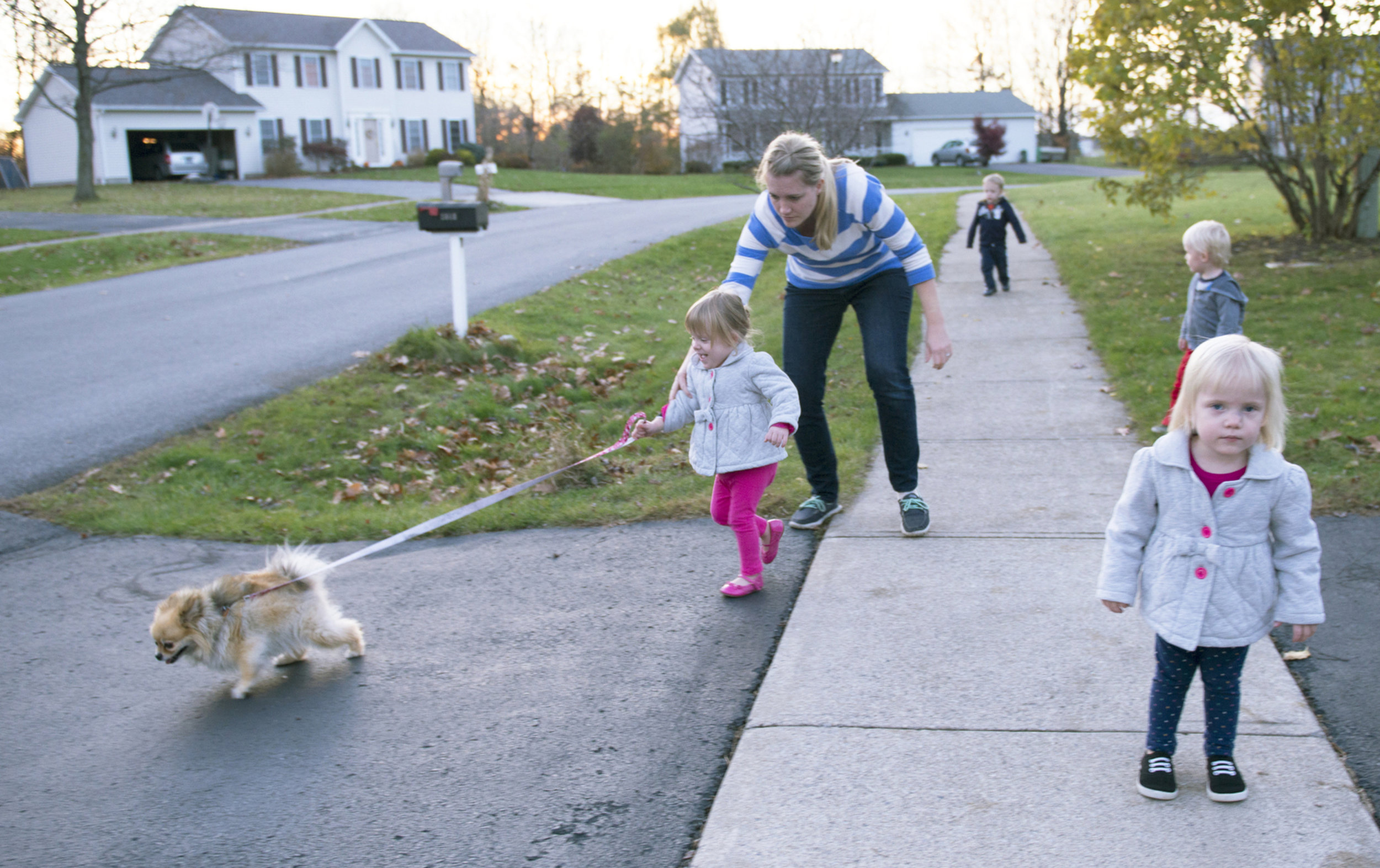 Courtney Larson leans in to grab Kylie Larson as their dog, Isabel heads toward the street on one of their walks on Nov. 10, 2015. Courtney tries to get them out of the house as much as possible, walks before bed help to tire them out.