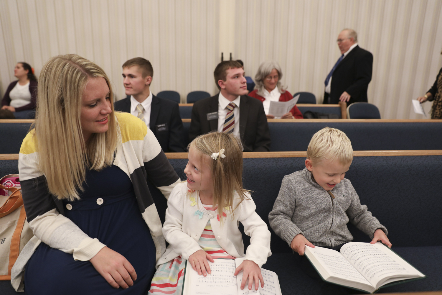 Courtney, Ashlyn, and Cooper look through a song book before the sacrament meeting begins on Oct. 23, 2016 at The church of Jesus Christ of Latter-day Saints Geneseo ward, Rochester Stake. The Larson's are Mormon instilling the word of God, good faith, and importance of family into their children.