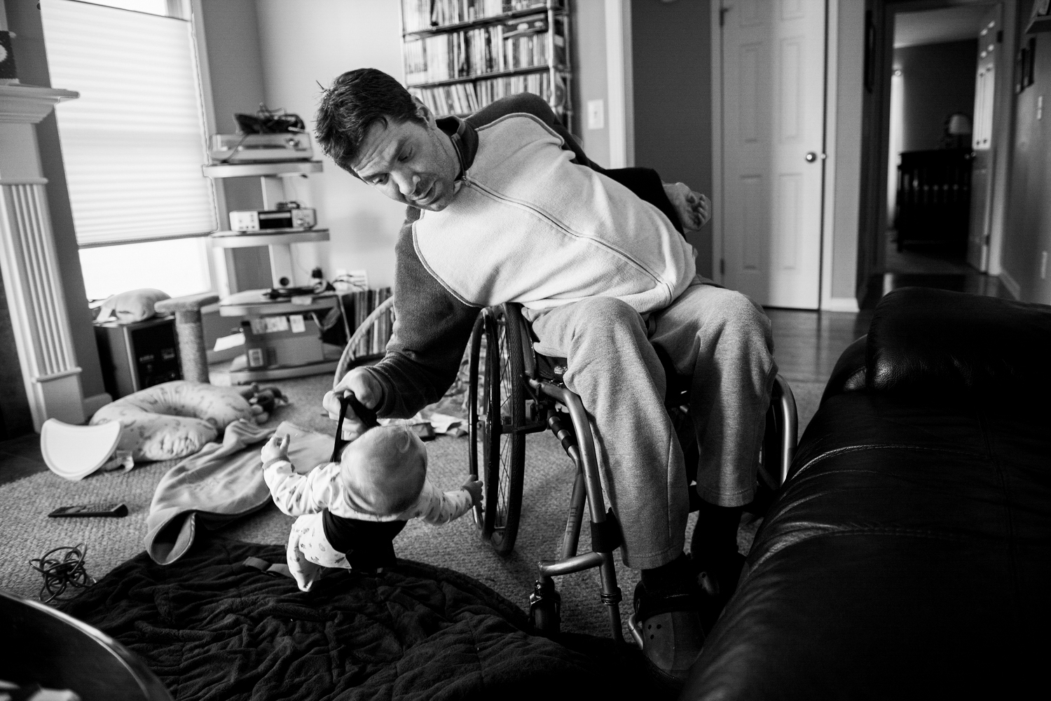 David lifts his son, Duncan onto his lap to put him down for a nap.Since David only has use of his right arm, which is weak he has created a device to lift Duncan up and down carefully to help. He worries when his son is over 25 pounds,he might not be able to lift him.