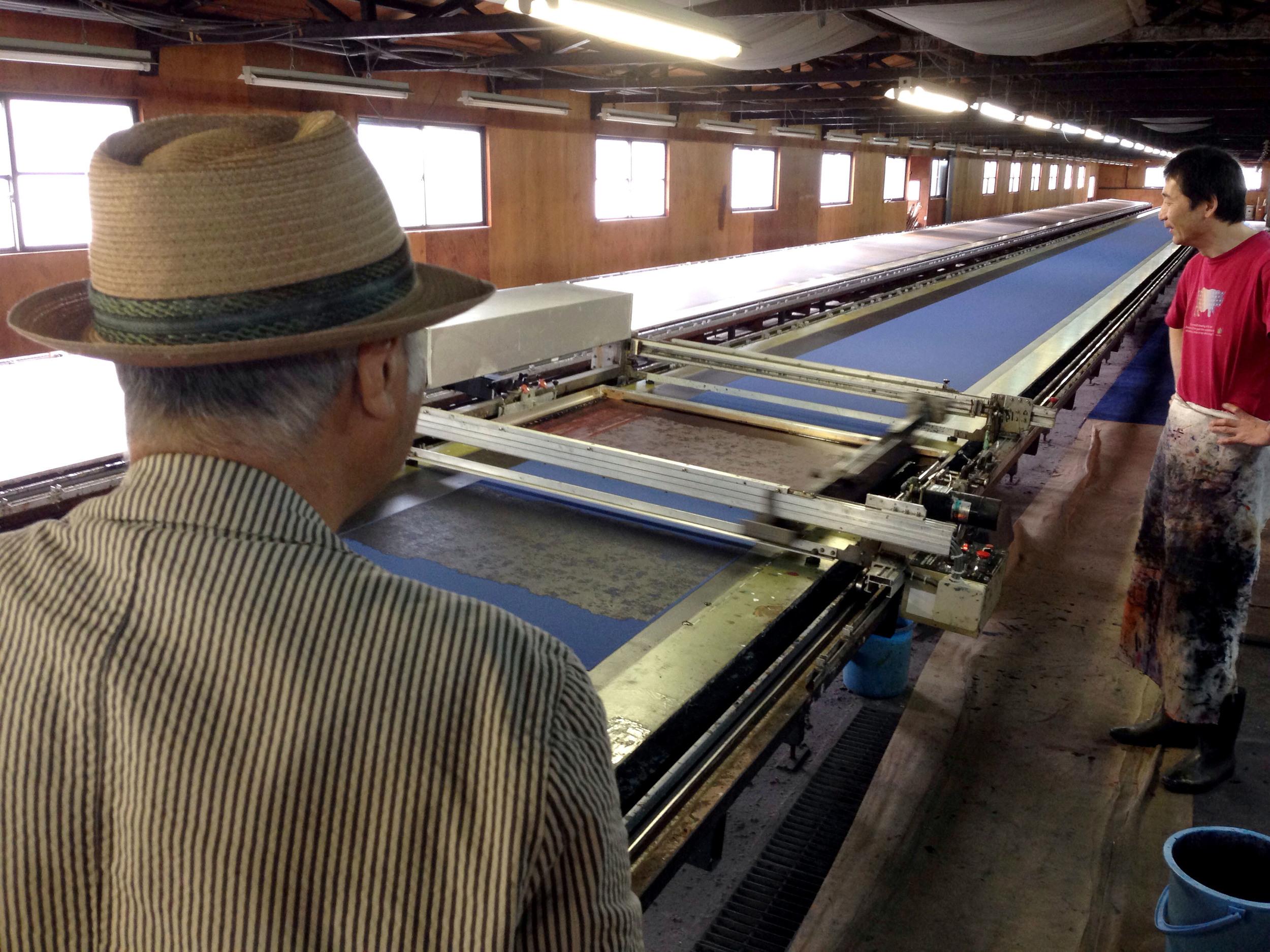 ROCCO's print designer, Minoru Ichimura, observes screen-printing in progress.