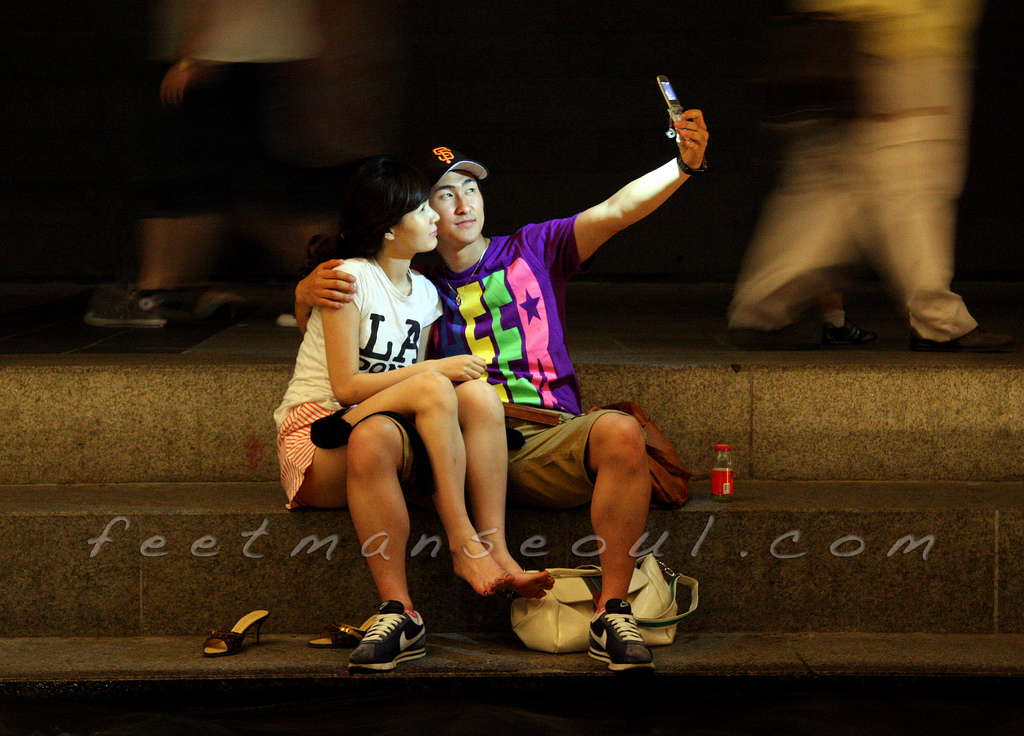 A couple takes a selfie downtown at the Cheonggye Stream.