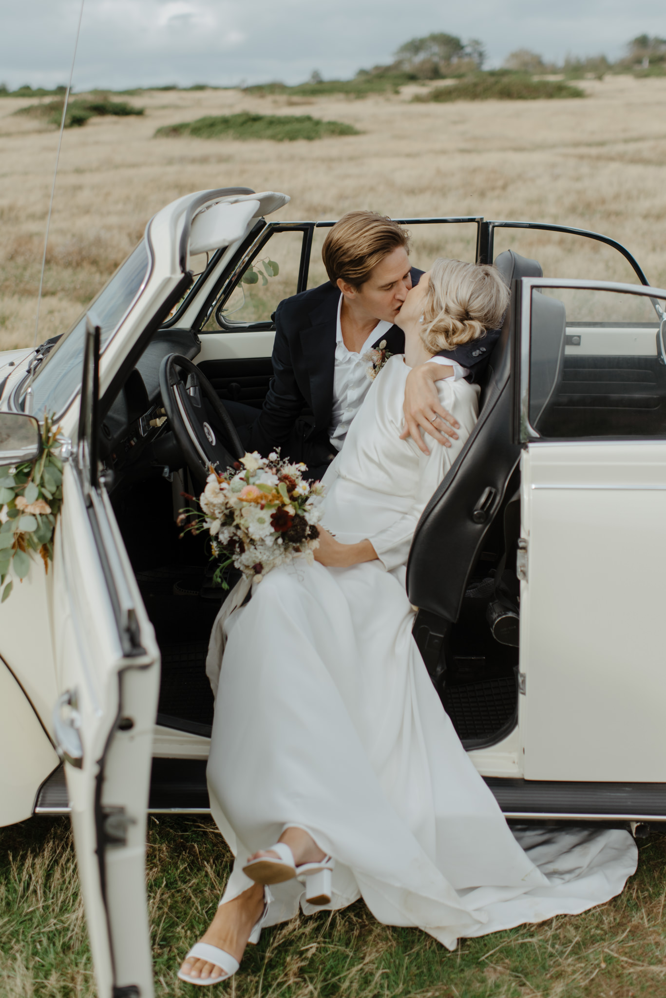 Chic newlyweds posing in their car