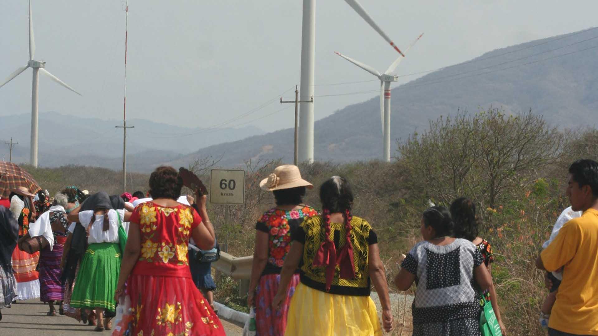 Indigenous communities walk past a large wind farm in Oaxaca, Mexico