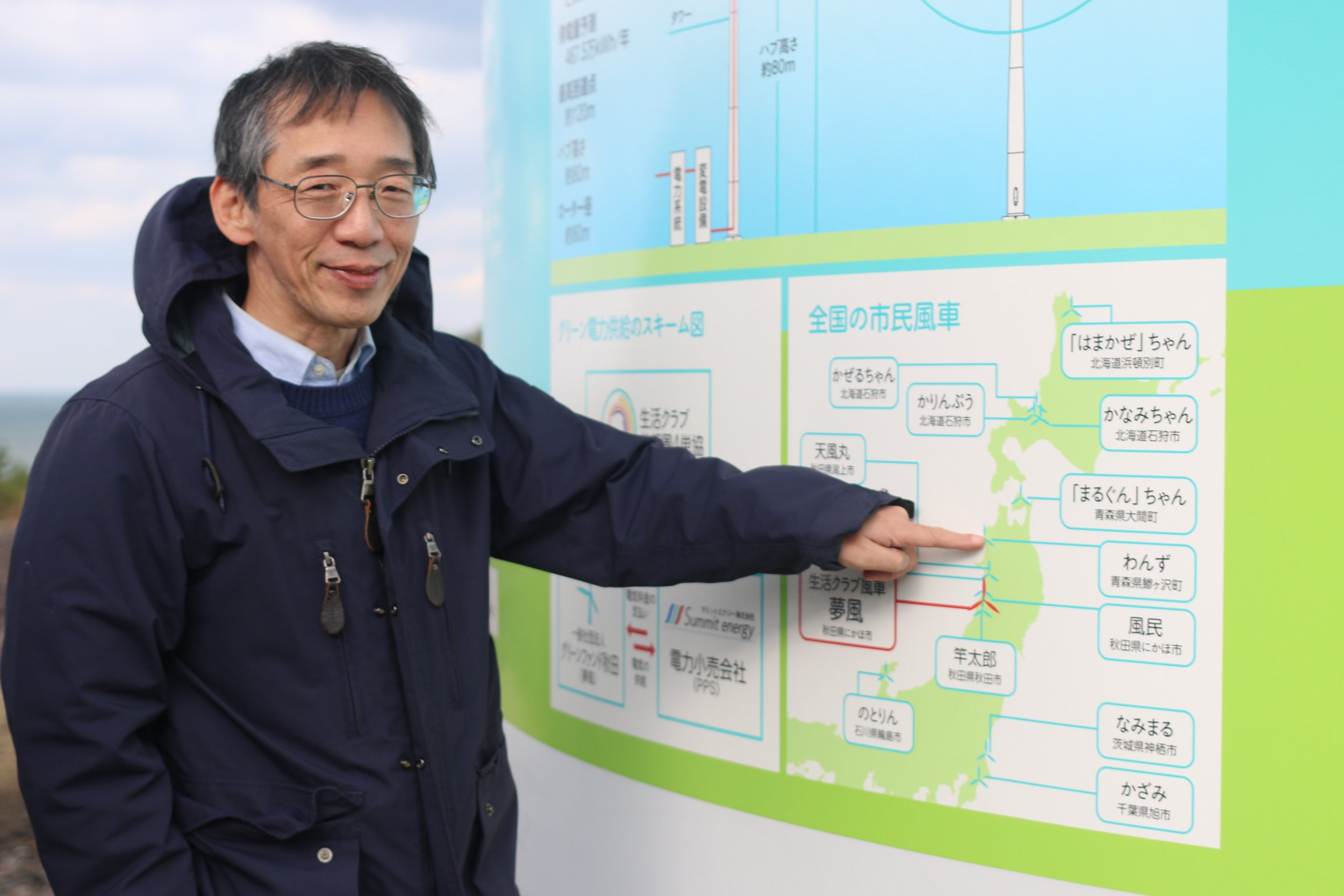 Community wind: an insurgent breed of energy in Japan.  This is Dr. Yasushi Maruyama, who has written a lot about Japanese community renewables, and also helps develop projects.  That's the base of a community wind turbine, with a map showing several of Japan's community wind project locations.  Photo:  Camilla S. Rose .
