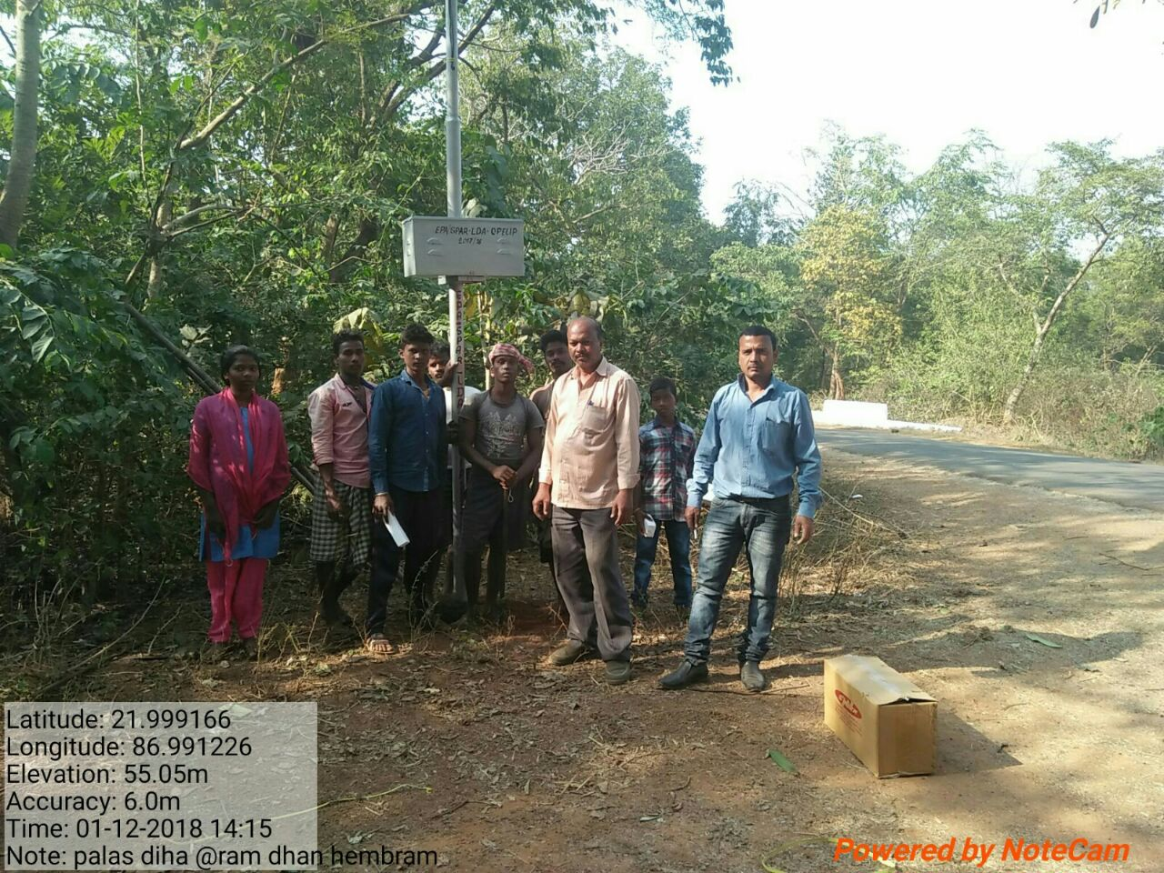 Bindu Kumar of Urjaa Samadhan, 3rd from right (cream shirt), with residents of a village in Mayurbhanj. A streetlight battery shown just above head-height.
