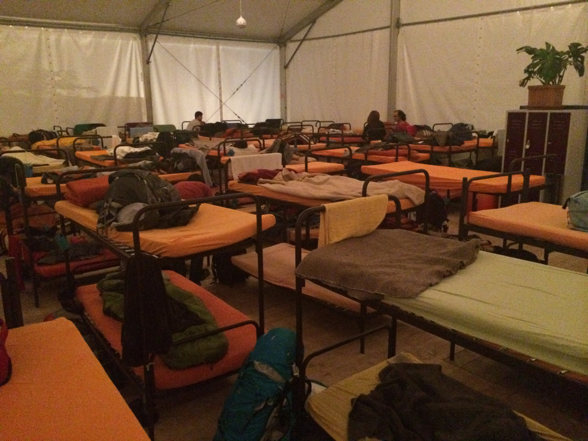 Ah, the luxury of my 100-person dorm. My bed is the one with the orange sheet on it... no not that one the one next to it... how can you not see it?