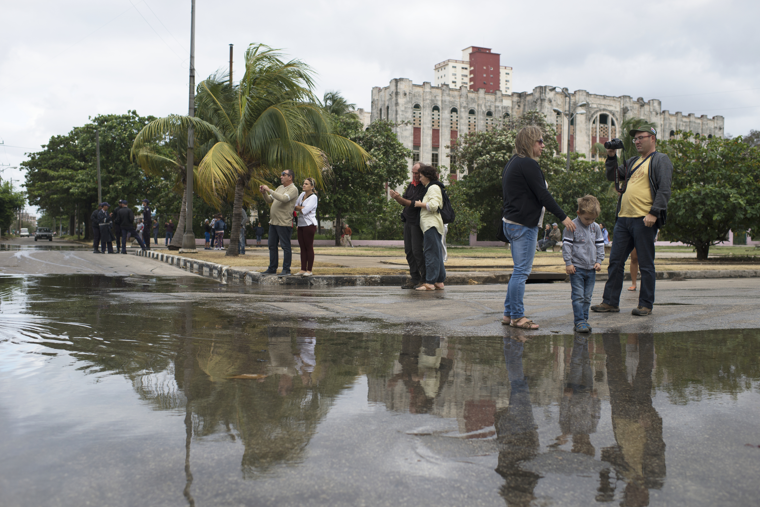 A family stands next to the flood waters in Havana, Cuba on Jan. 23, 2016.
