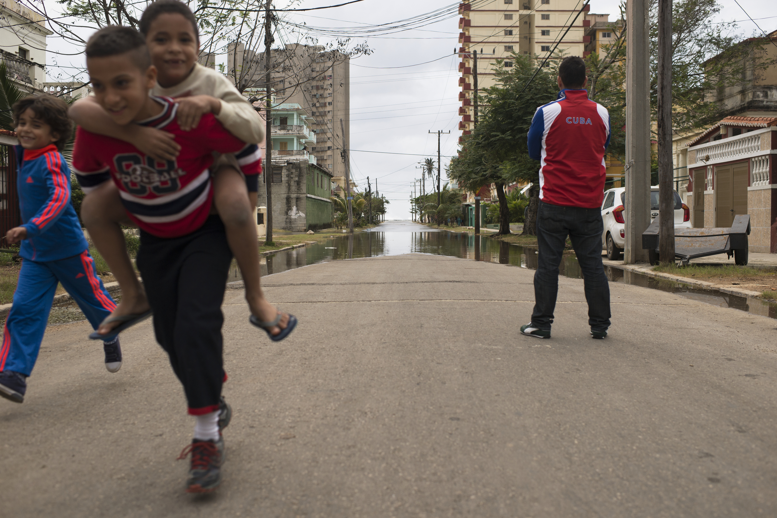 Children play as a man looks at the flood waters in Havana, Cuba on Jan. 23, 2016.
