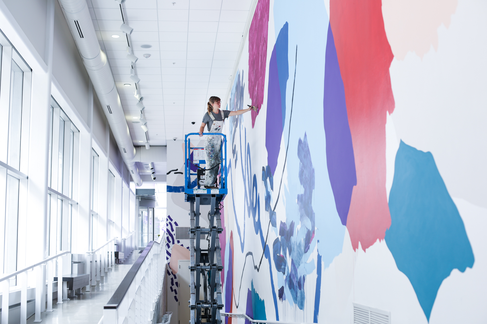 Heather Day paints the Pantone Color of the Year mural at the Urban Institute of Contemporary Art