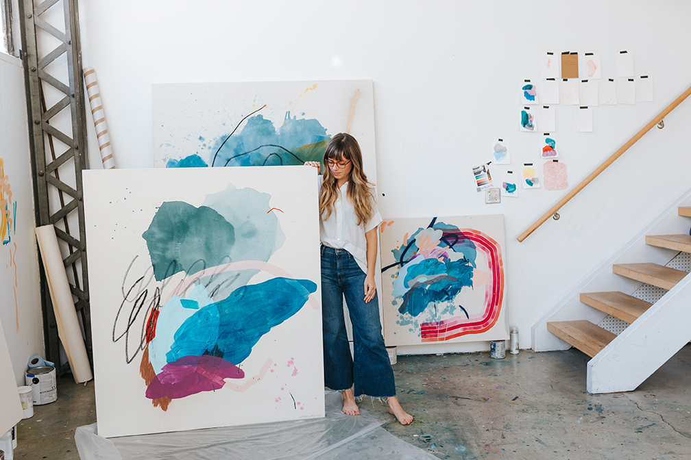 Heather Day stands with her painting at her studio in San Francisco