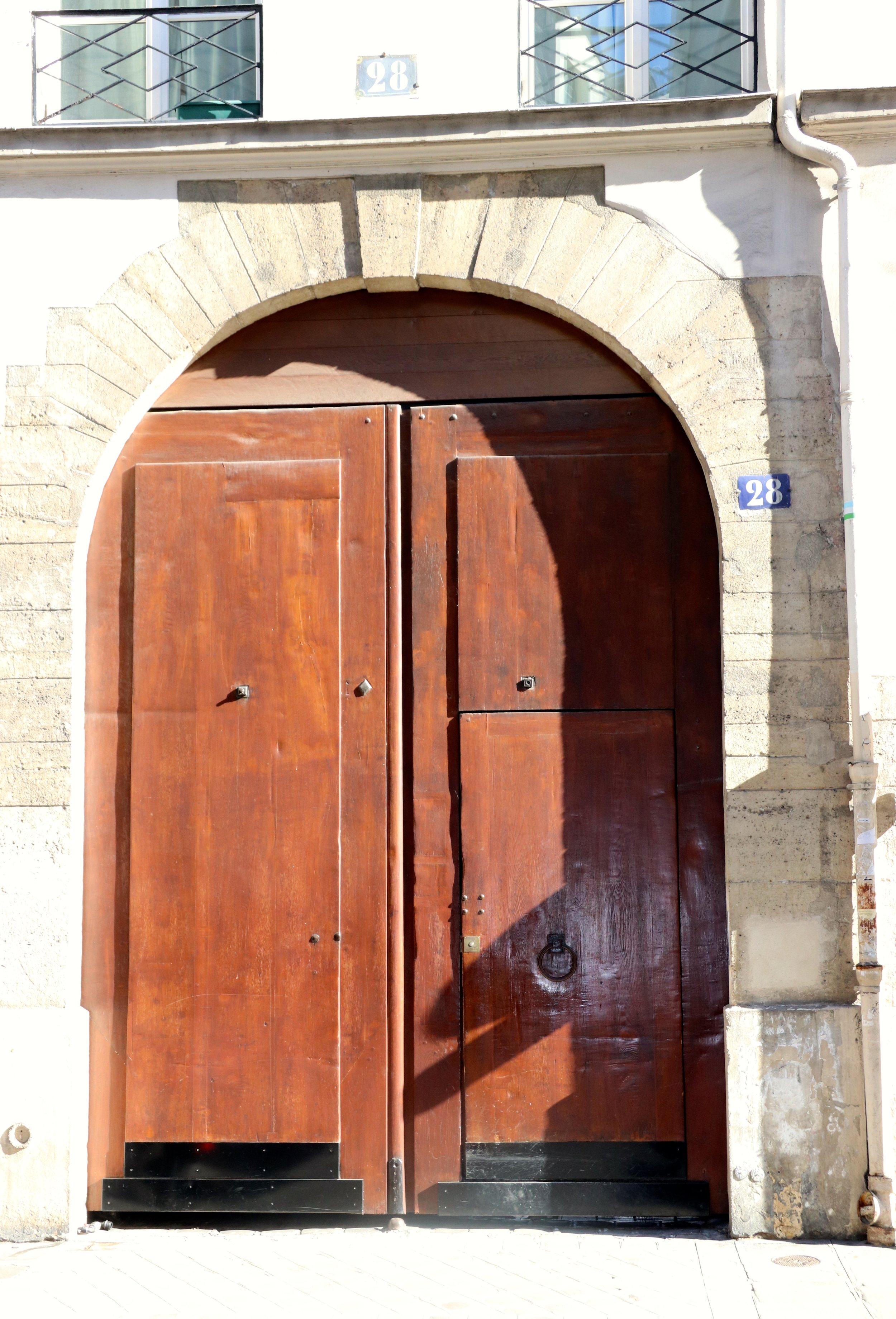 The huge, heavy door into the apartment building