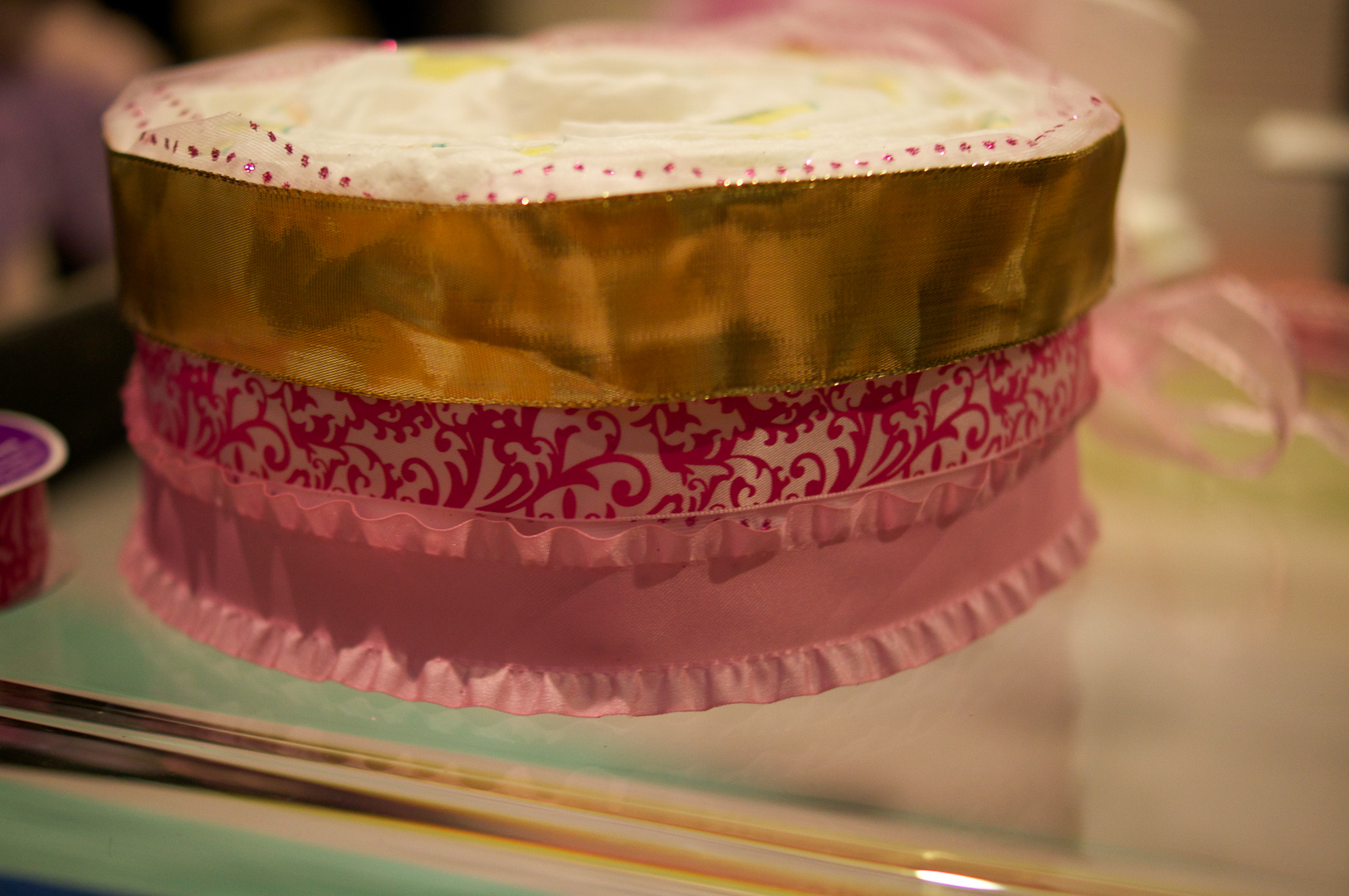 It's up to you how you want to decorate the cake with ribbons. I chose the pink double ruffled satin ribbon for the bottom, the pink satin damask for the middle, and a wide gold wired ribbon for the top. Designs are all up to you!