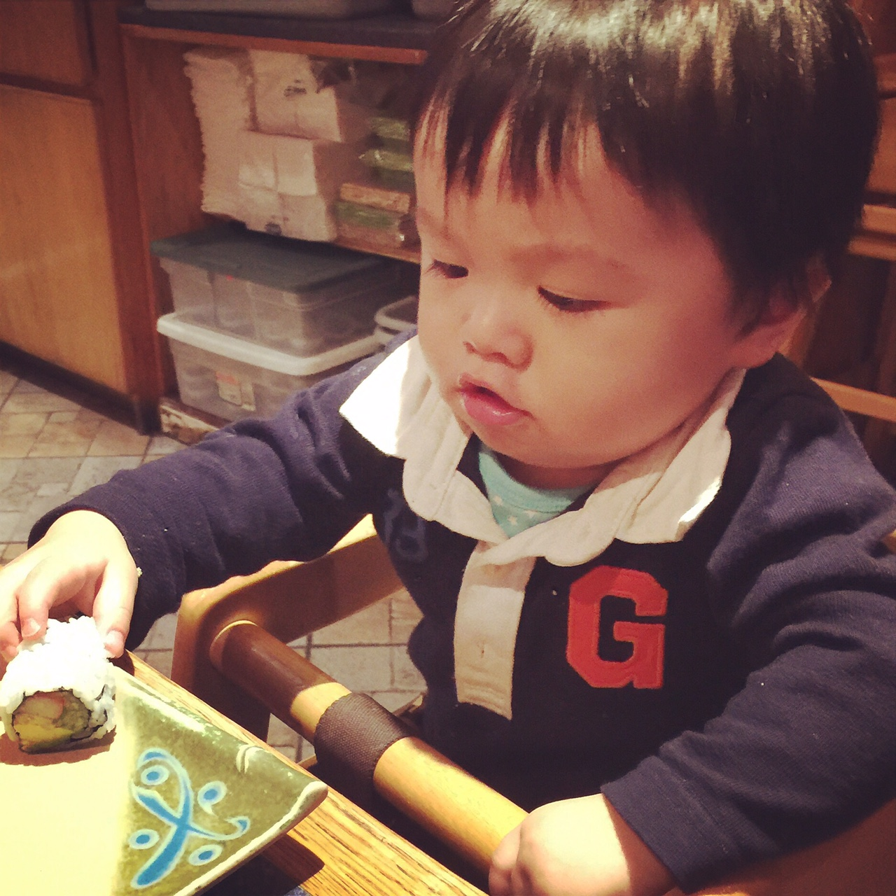 """Phil reaching for a piece of California roll at one of our favorite family sushi restaurants in NYC. Does he look like a girl, by the way? Someone said to us, """"Oh what a cute girl she is! G for girl, right?"""" Um..."""