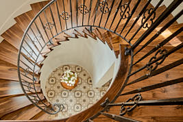 Spiral stairs with wood steps in Spanish Colonial Mansion.  Photograph by Dean Birinyi, interior photographer in San Francisco, CA.