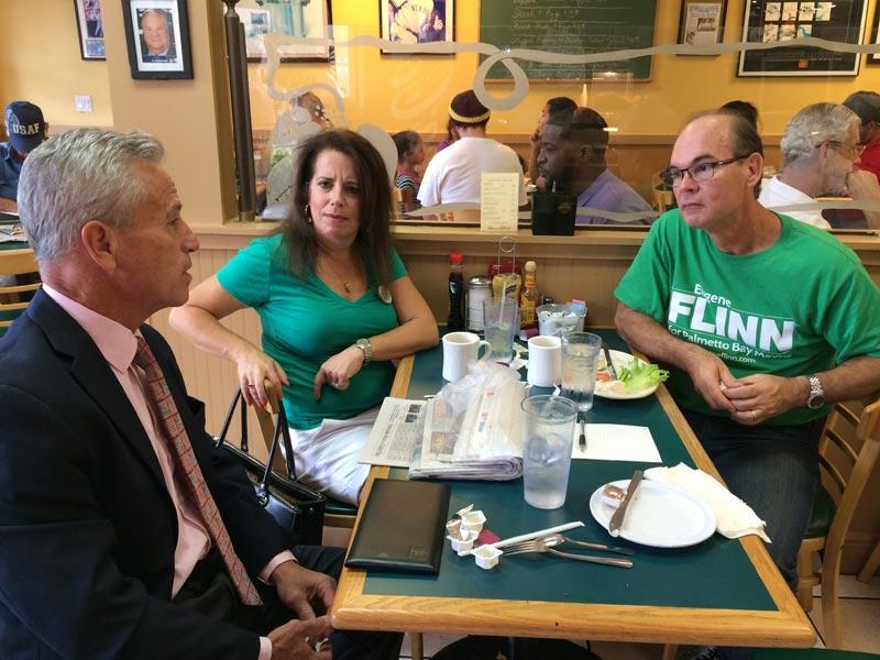 Scott Krugman (left) asks Eugene Flinn about his plans should he become mayor again as Flinn's wife  Alexandra looks on.