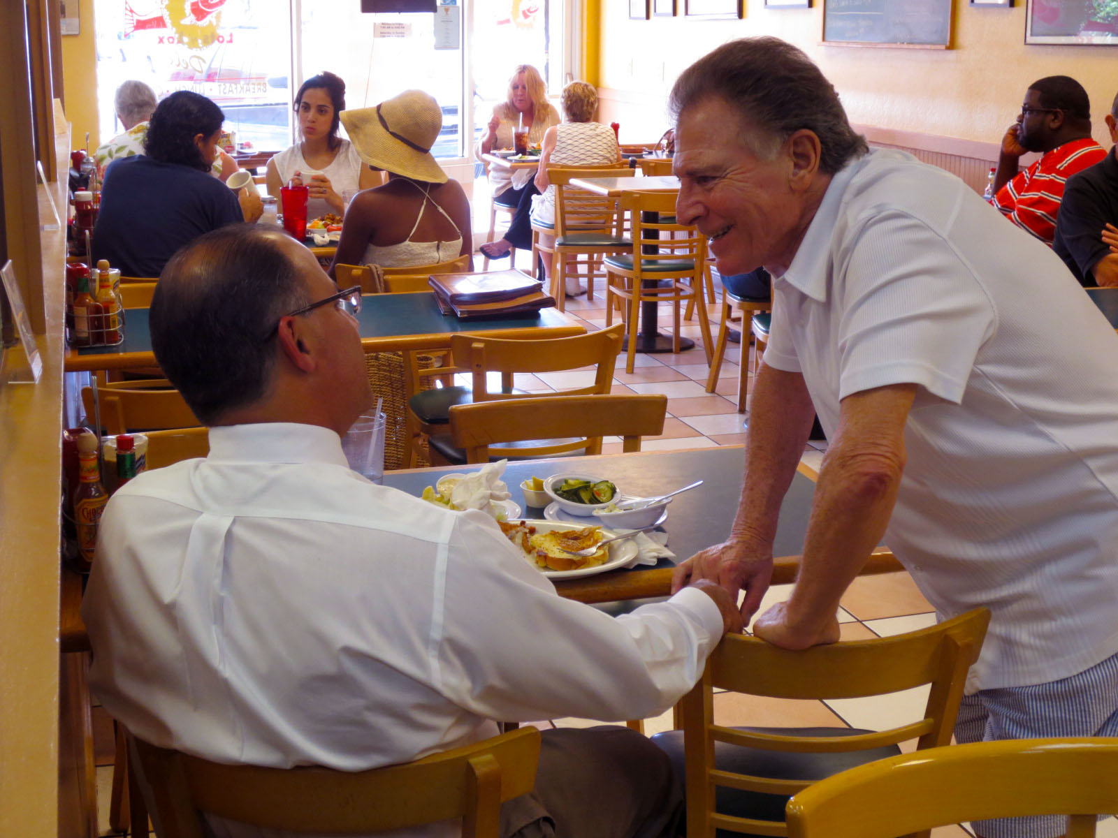 Owner Jimmy Poulos [right] welcomes a patron and makes sure things are just right