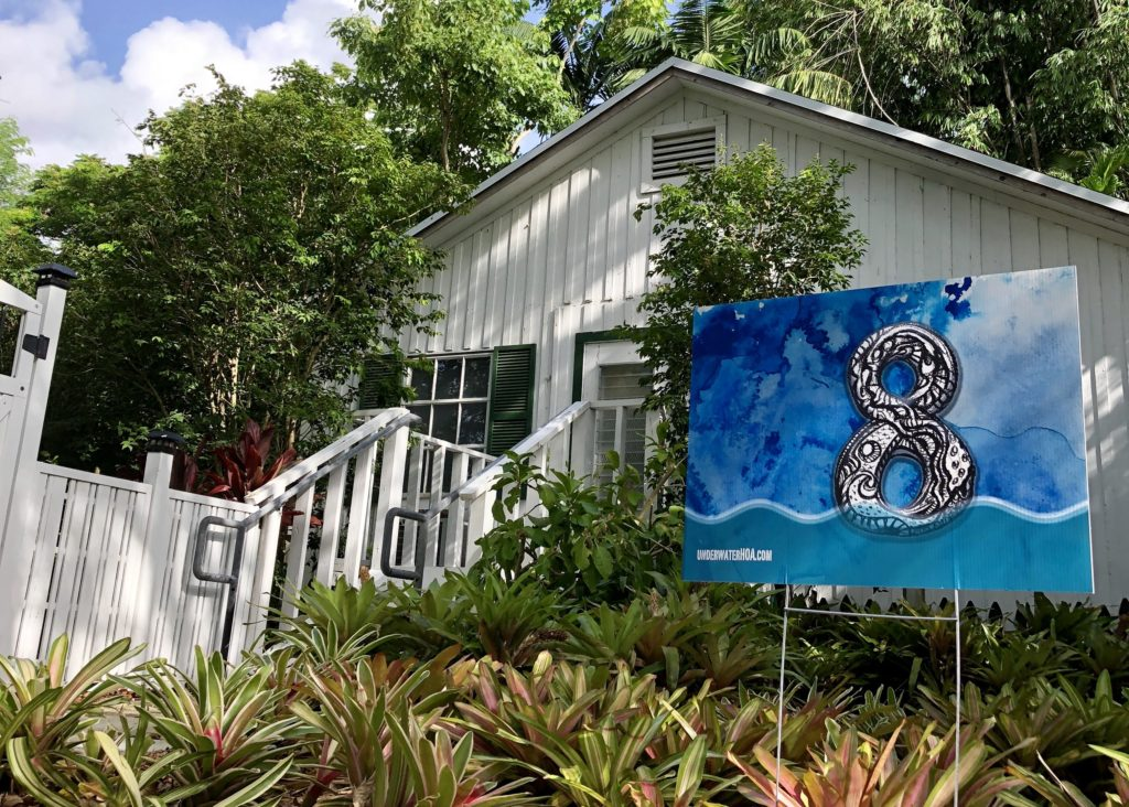 Outside Xavier Cortada's art installation is a working example of the yard signs now placed in many Pinecrest yards.