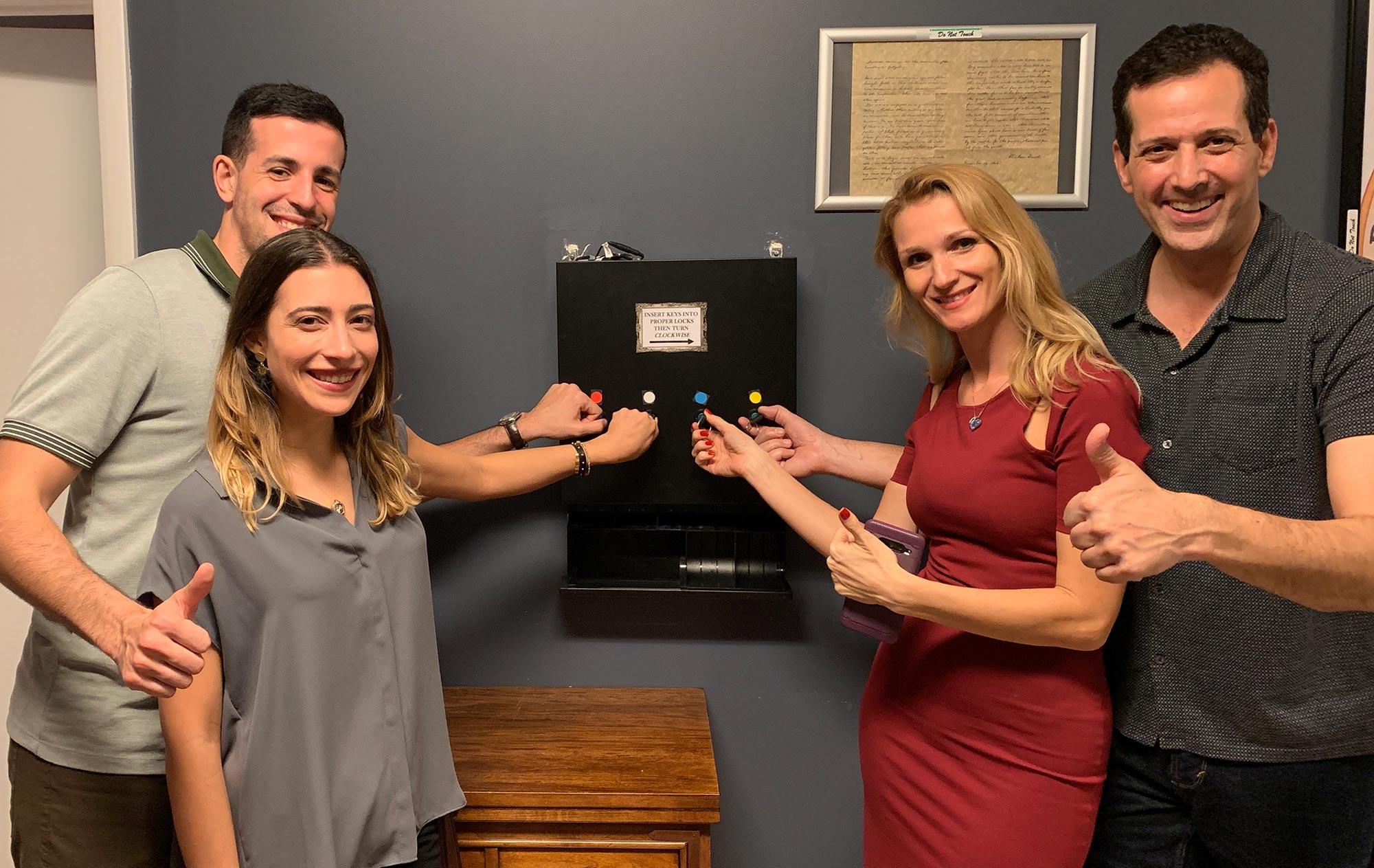 David Demarchena, Nicole Rosa, Ekaterina Khayrulina and Hal Feldman turn keys simultaneously to unlock a new secret at  The Great Escape Room