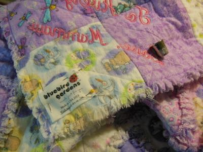 BLUEBIRD GARDENS QUILT CARE LABEL HAND SEWN ON BACK OF A FLANNEL RAG BABY QUILT