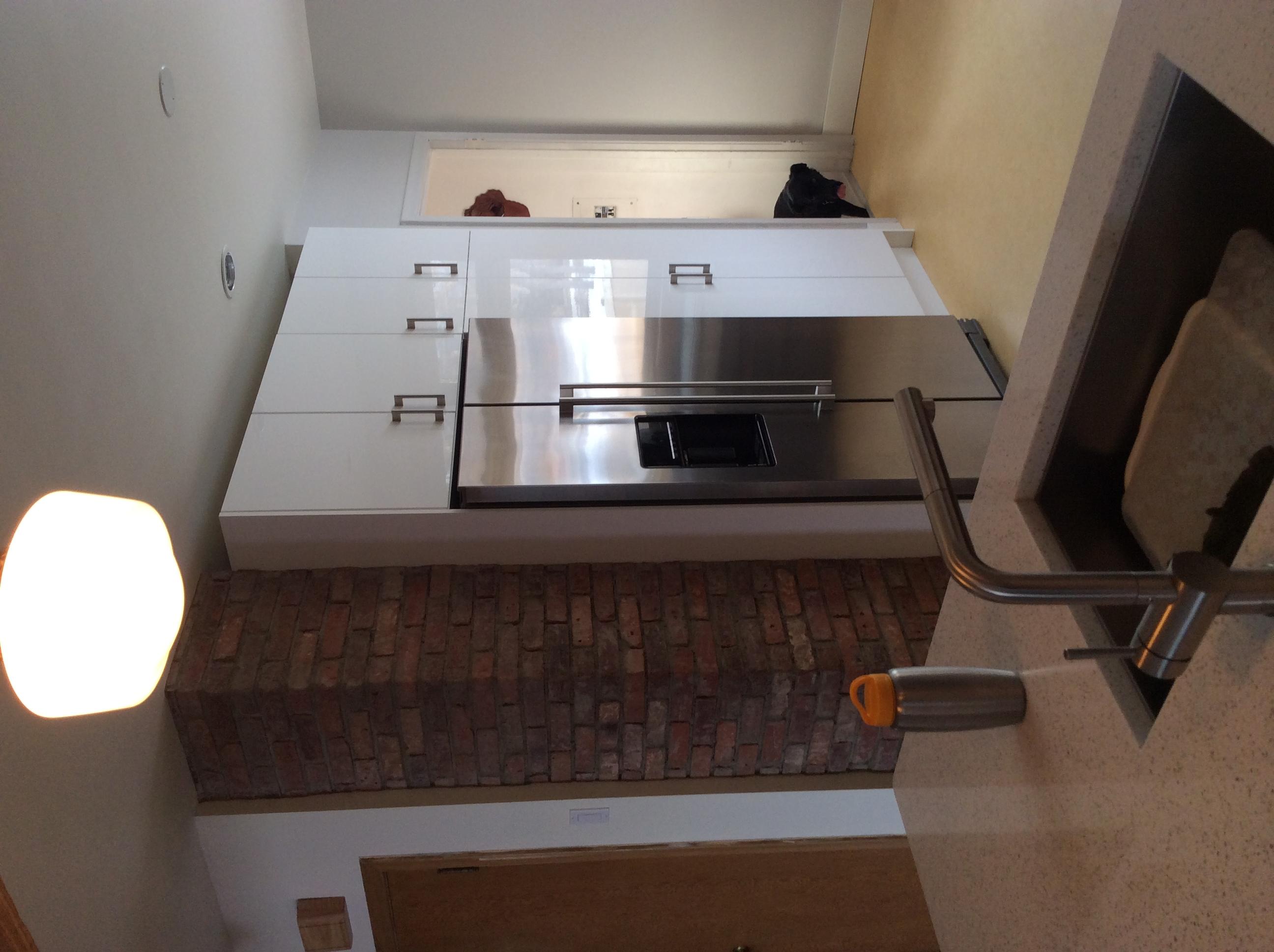 Exposed brick chimney, gloss white Ikea cabinets.