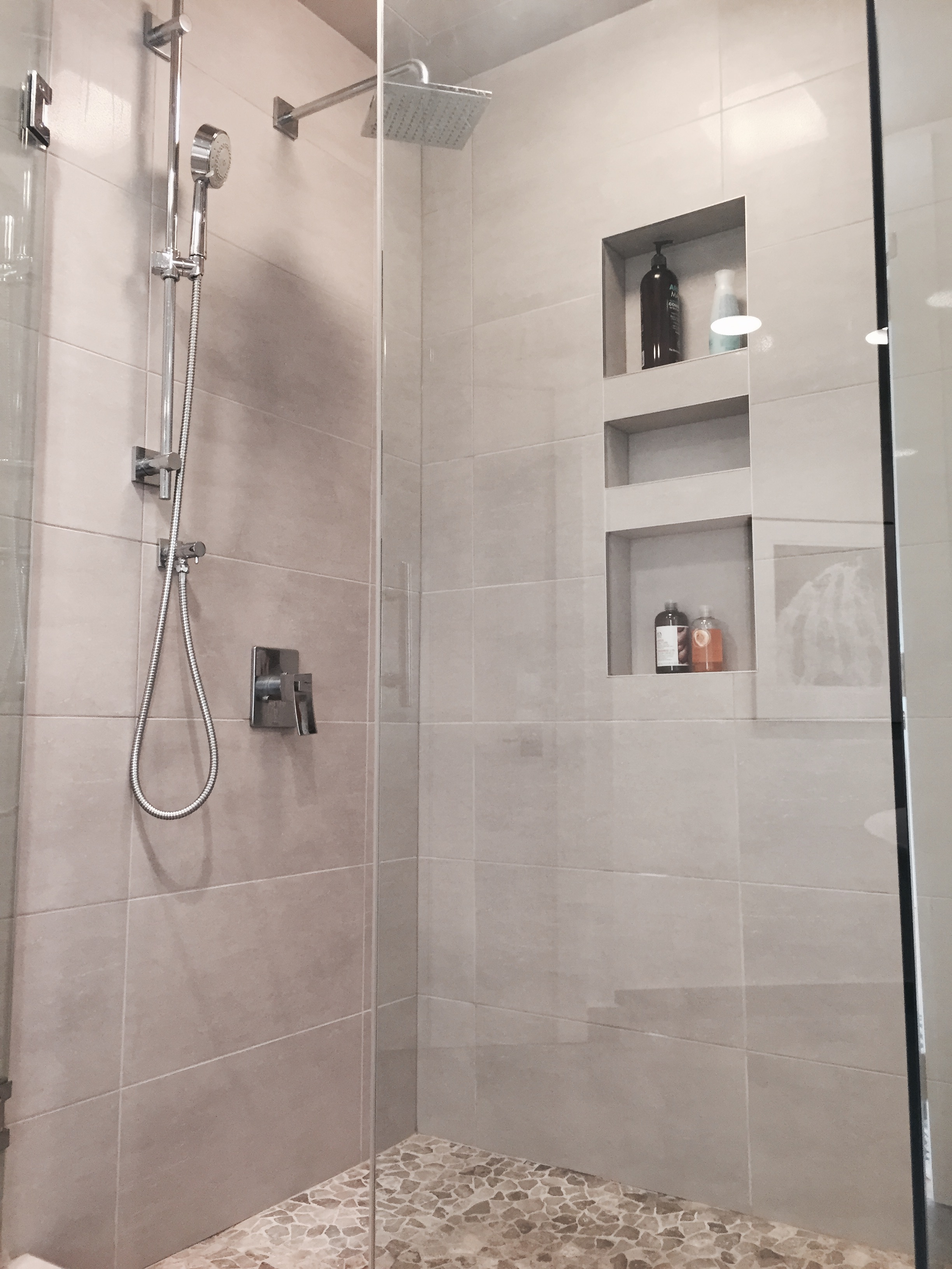 Custom Shower, pebble floor and recessed shelves.