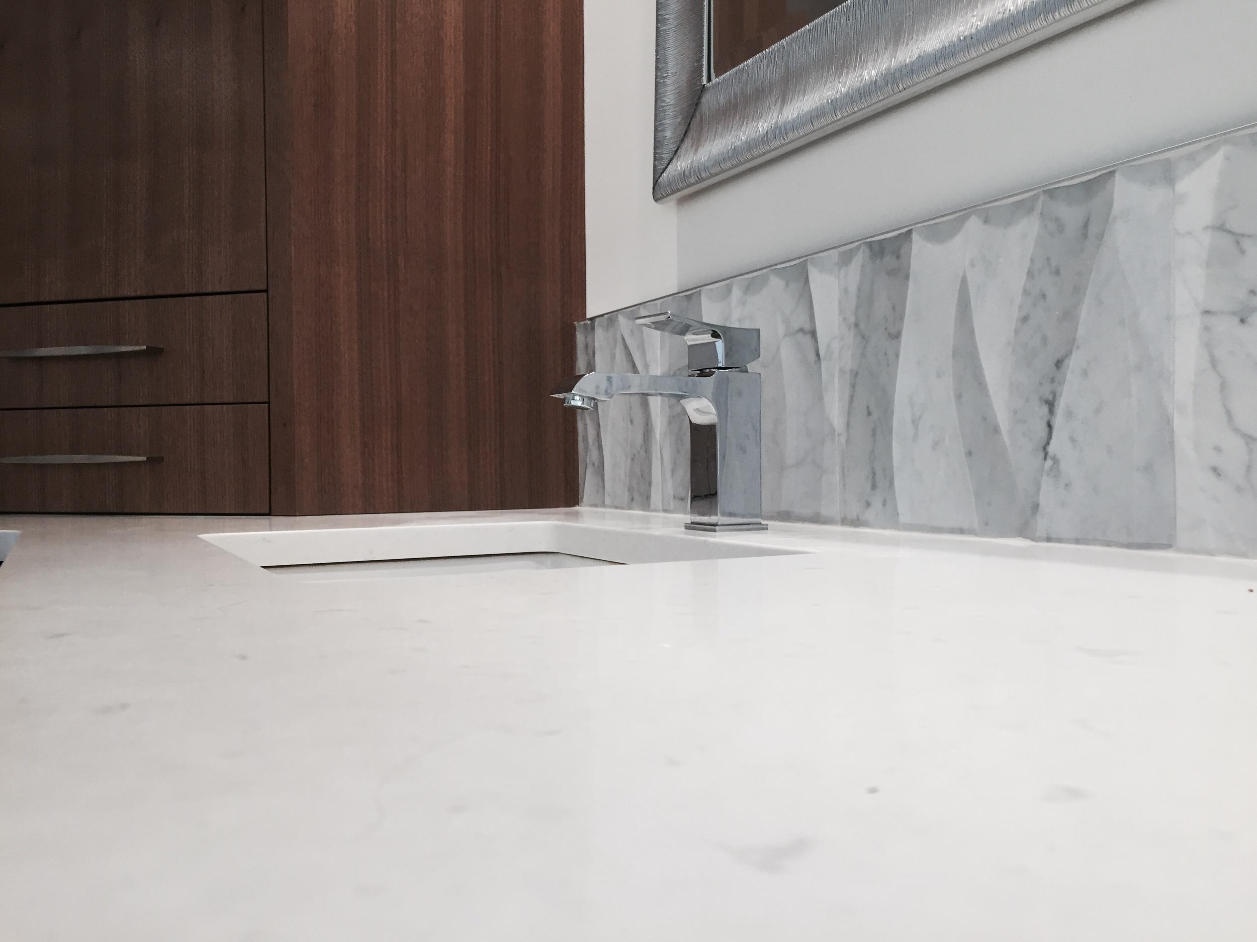 Quartz countertops, custom walnut cabinetry, Ziva Leaves by Artistic Tile.