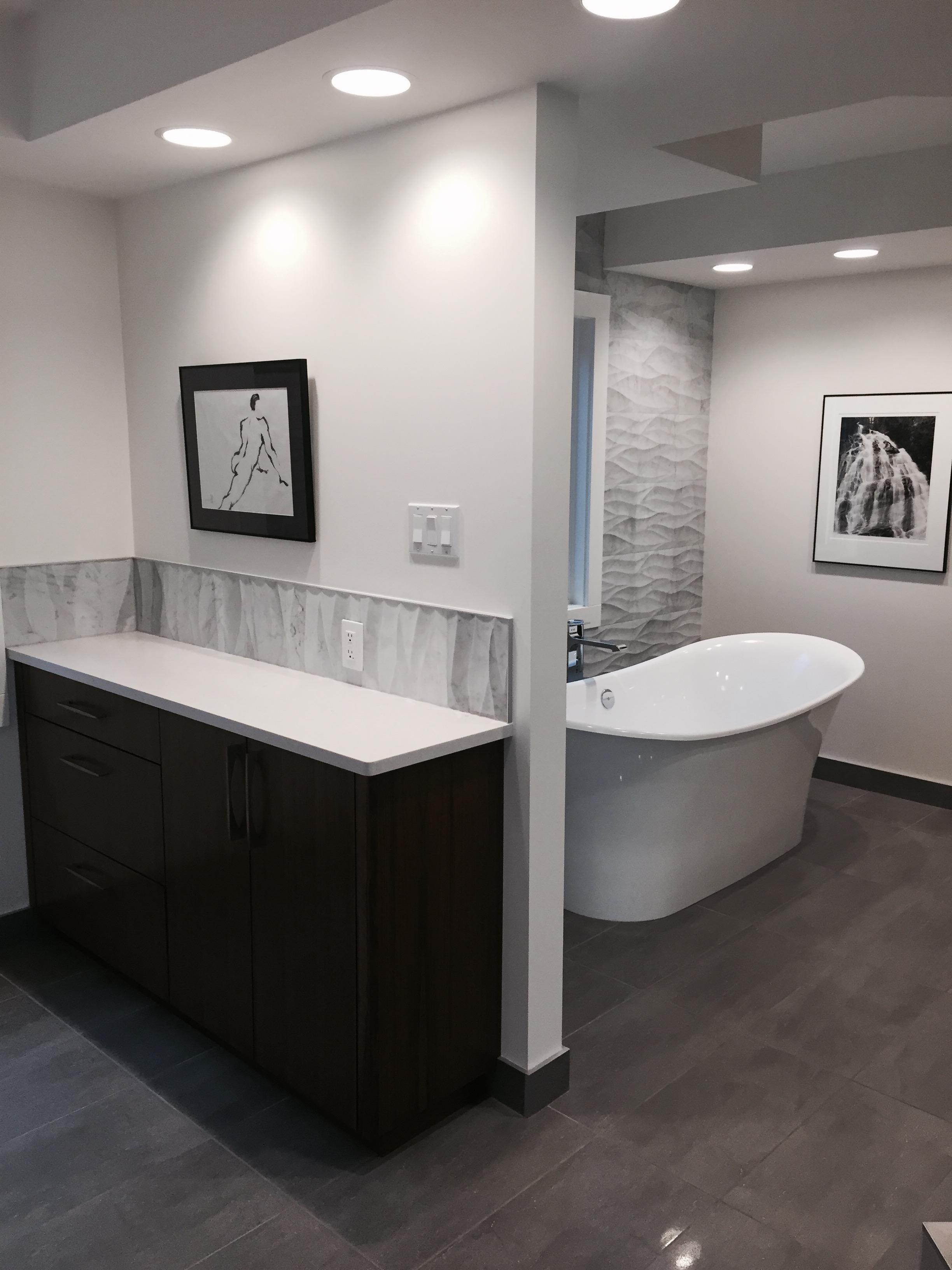 Custom walnut cabinetry, quartz countertops, volcanic limestone bathtub, bianca carrara tile.