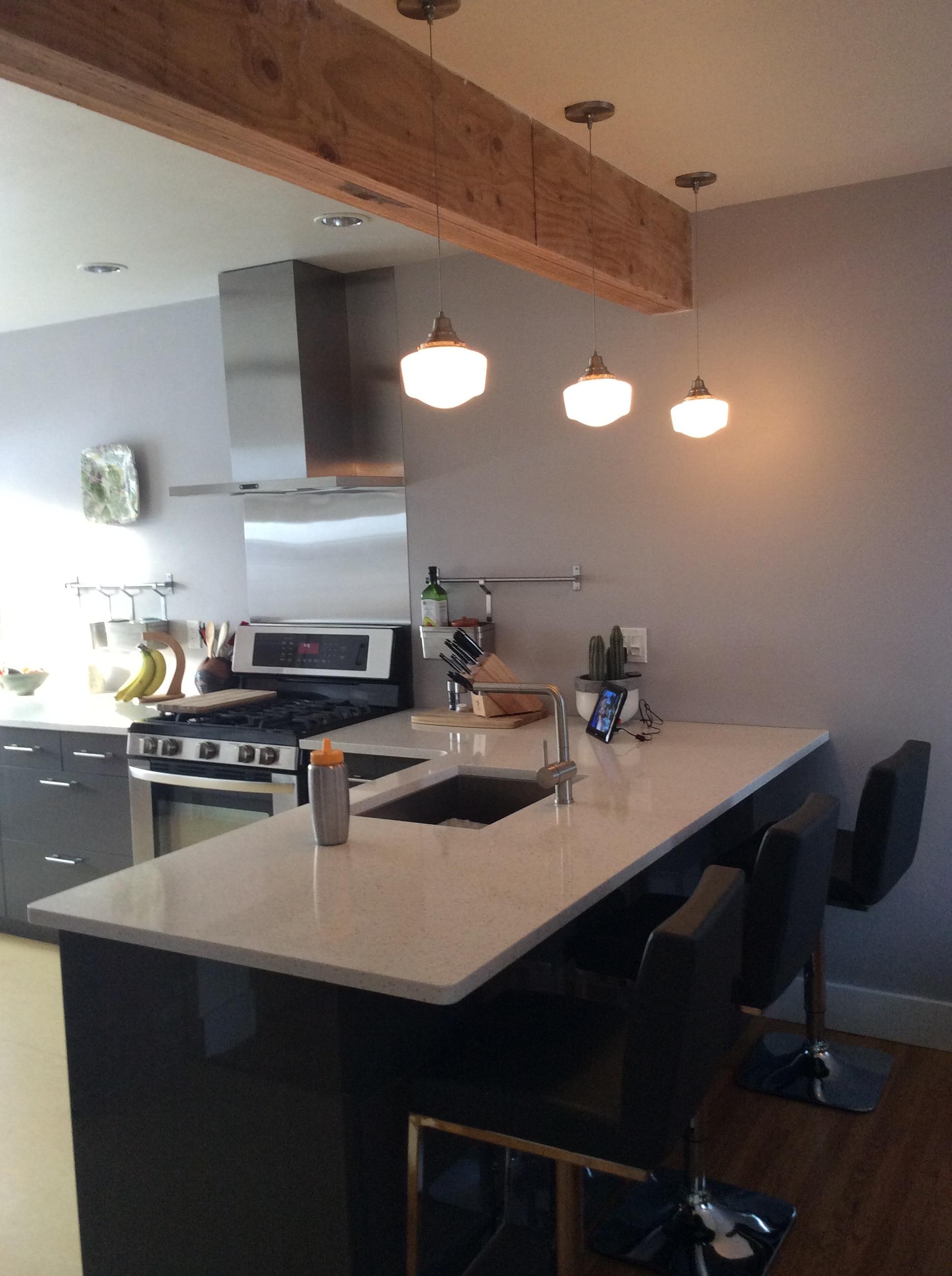 Schoolhouse pendant light fixtures, quartz countertops, Ikea cabinets, rustic support beam.