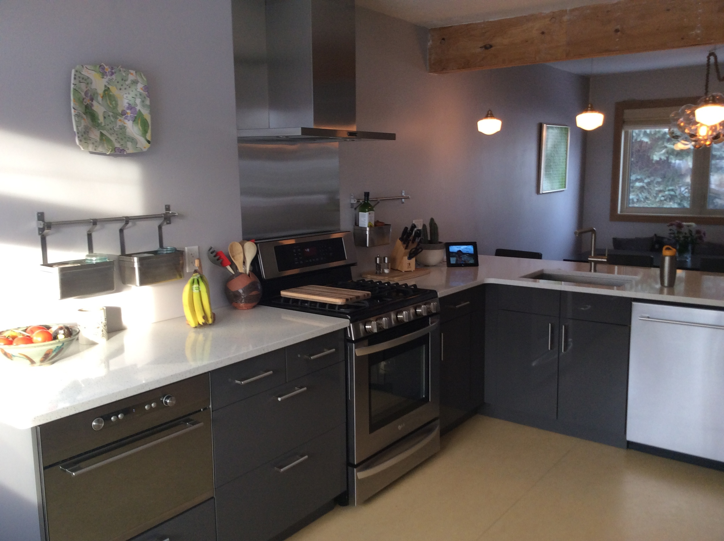 Ikea cabinets, Stainless steel backsplash, rustic wood support beam, quartz countertops, schoolhouse pendant lights.