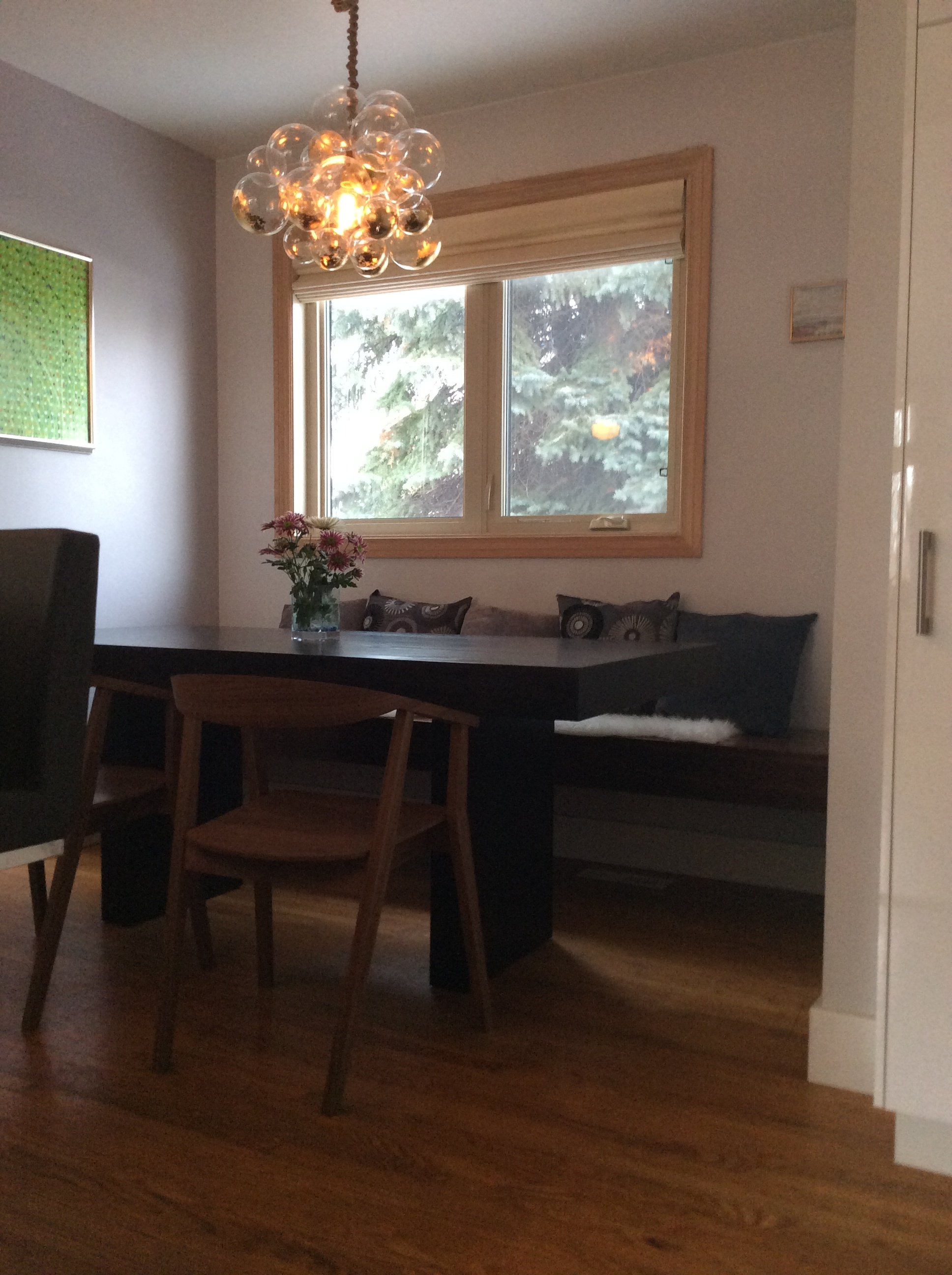 Dining table with floating bench seat and handmade chandelier.