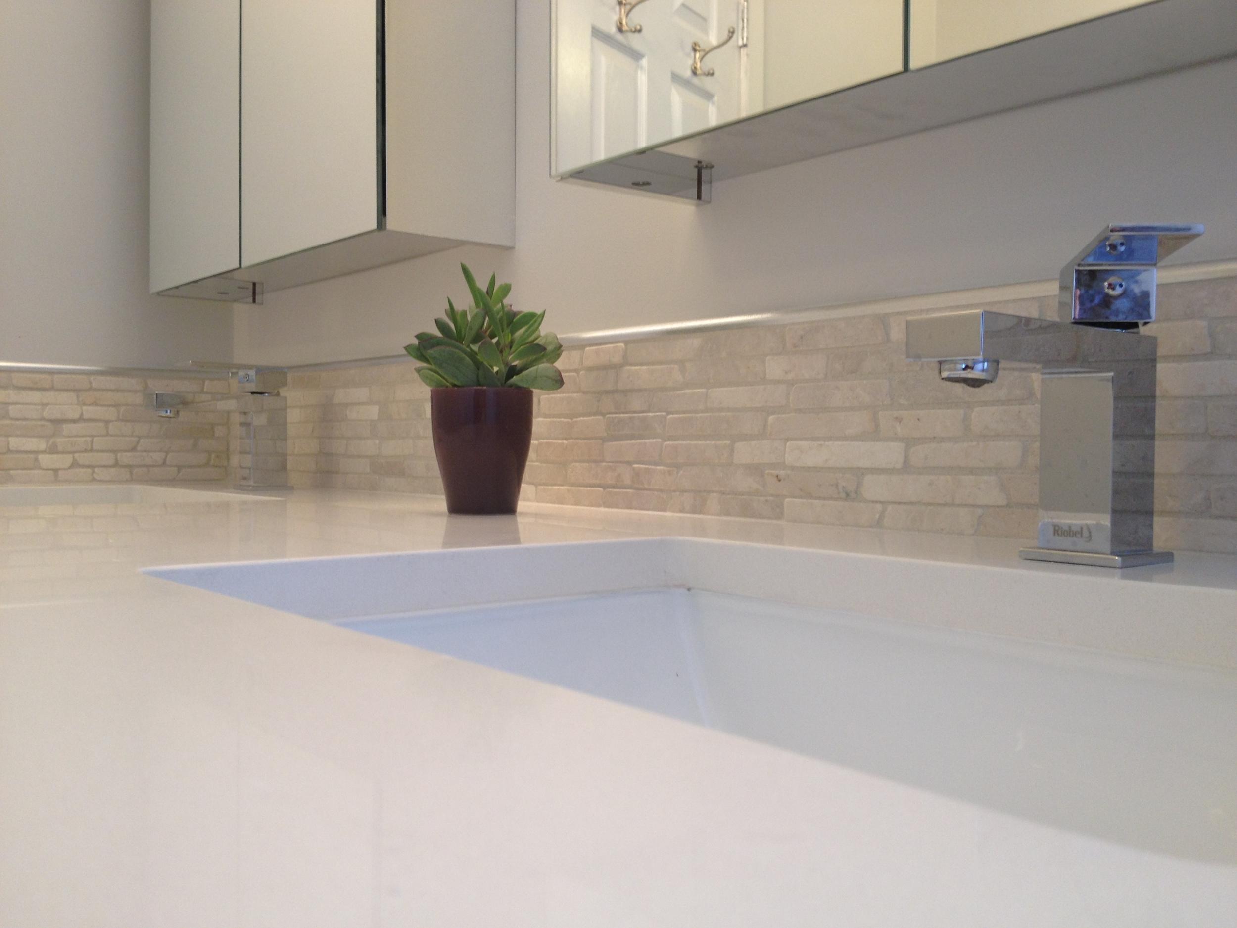 Quartz countertops, stone backsplash and double vanity.