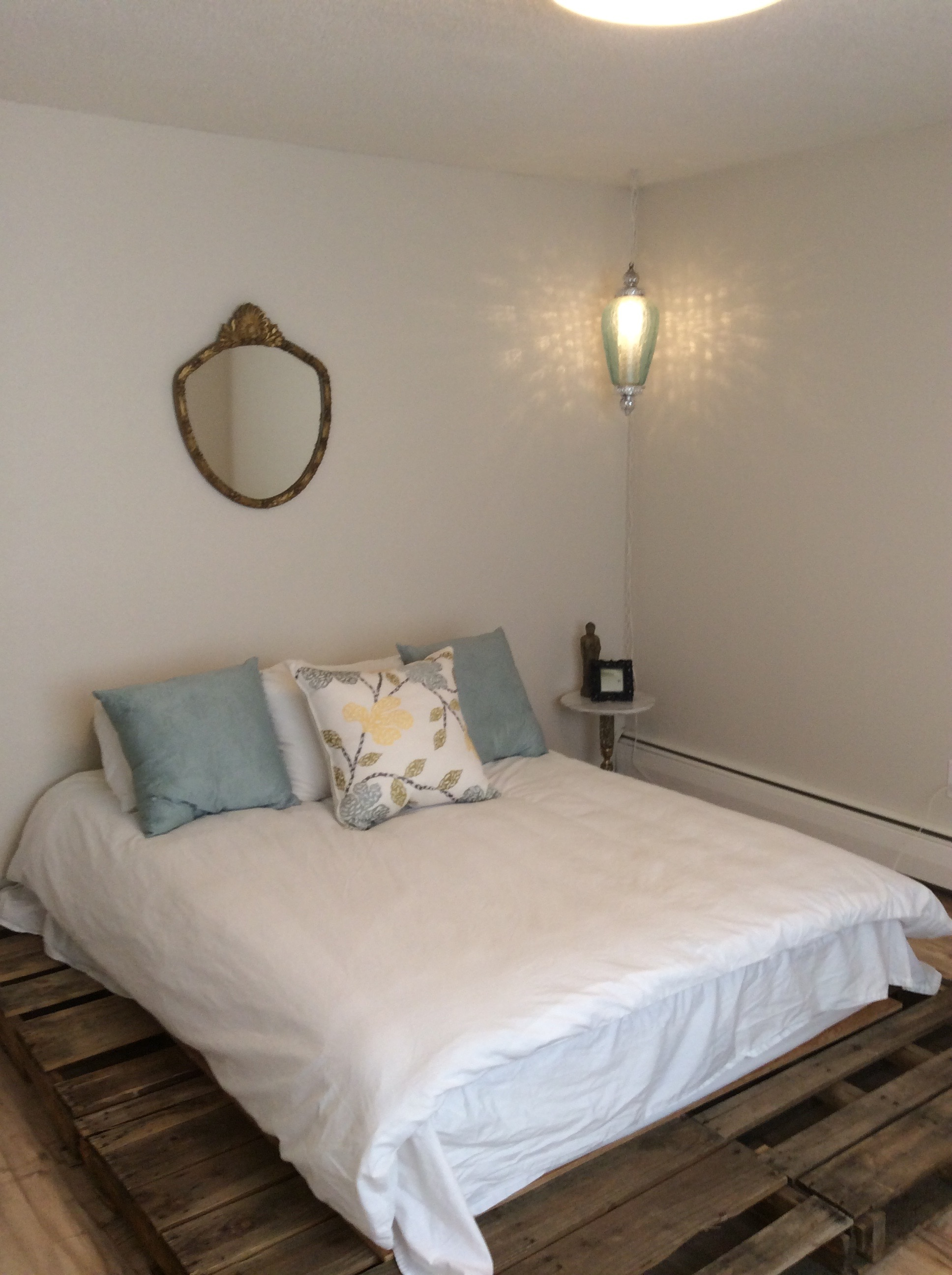 Pallet bed base, vintage blue lamp, and vintage mirror.