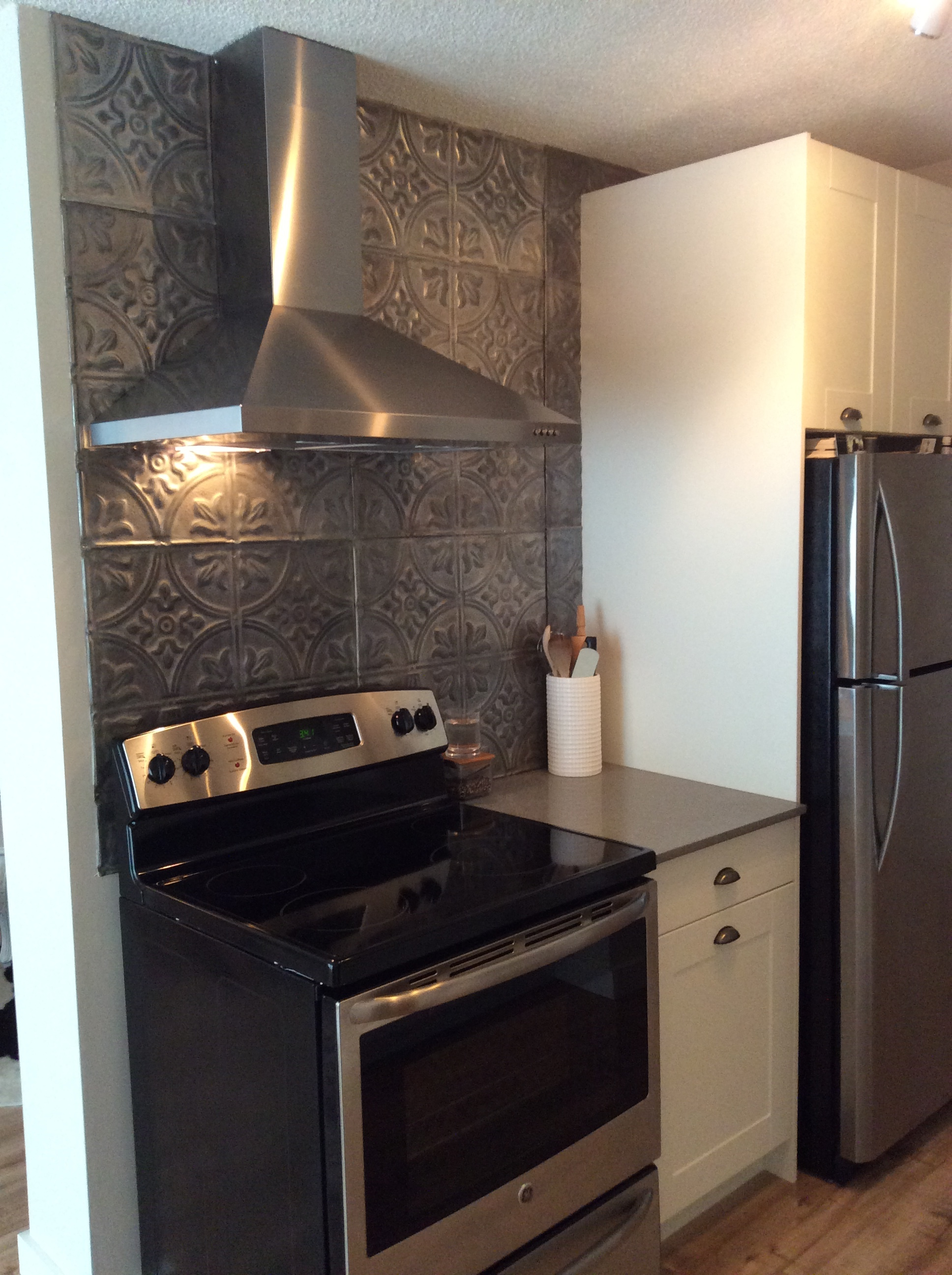 Ikea kitchen, tin tile backsplash, and stainless steel range and range hood.