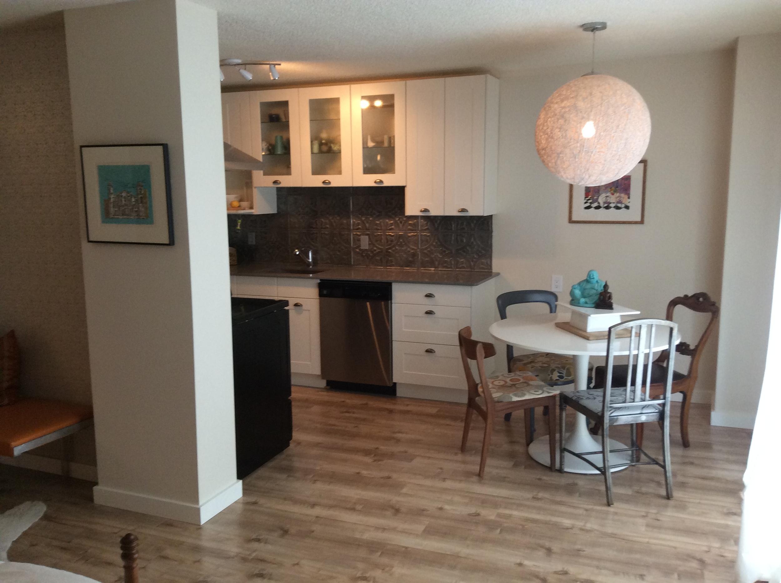 Structube String Light, tulip table, refurbished vintage chairs, Ikea kitchen, tin tile backsplash.