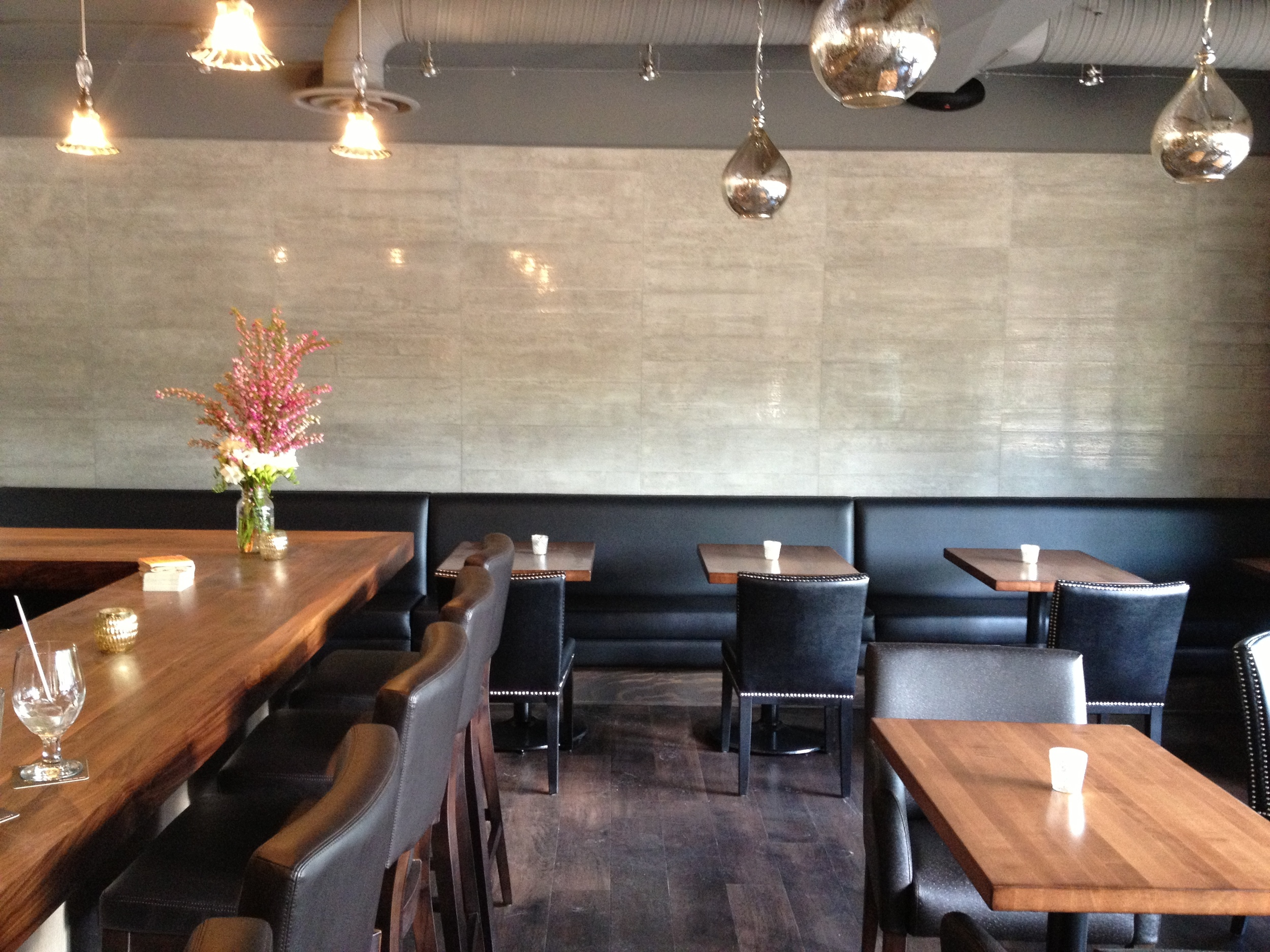 Polished concrete look tile, custom walnut bar top, black leather floating bench seat.