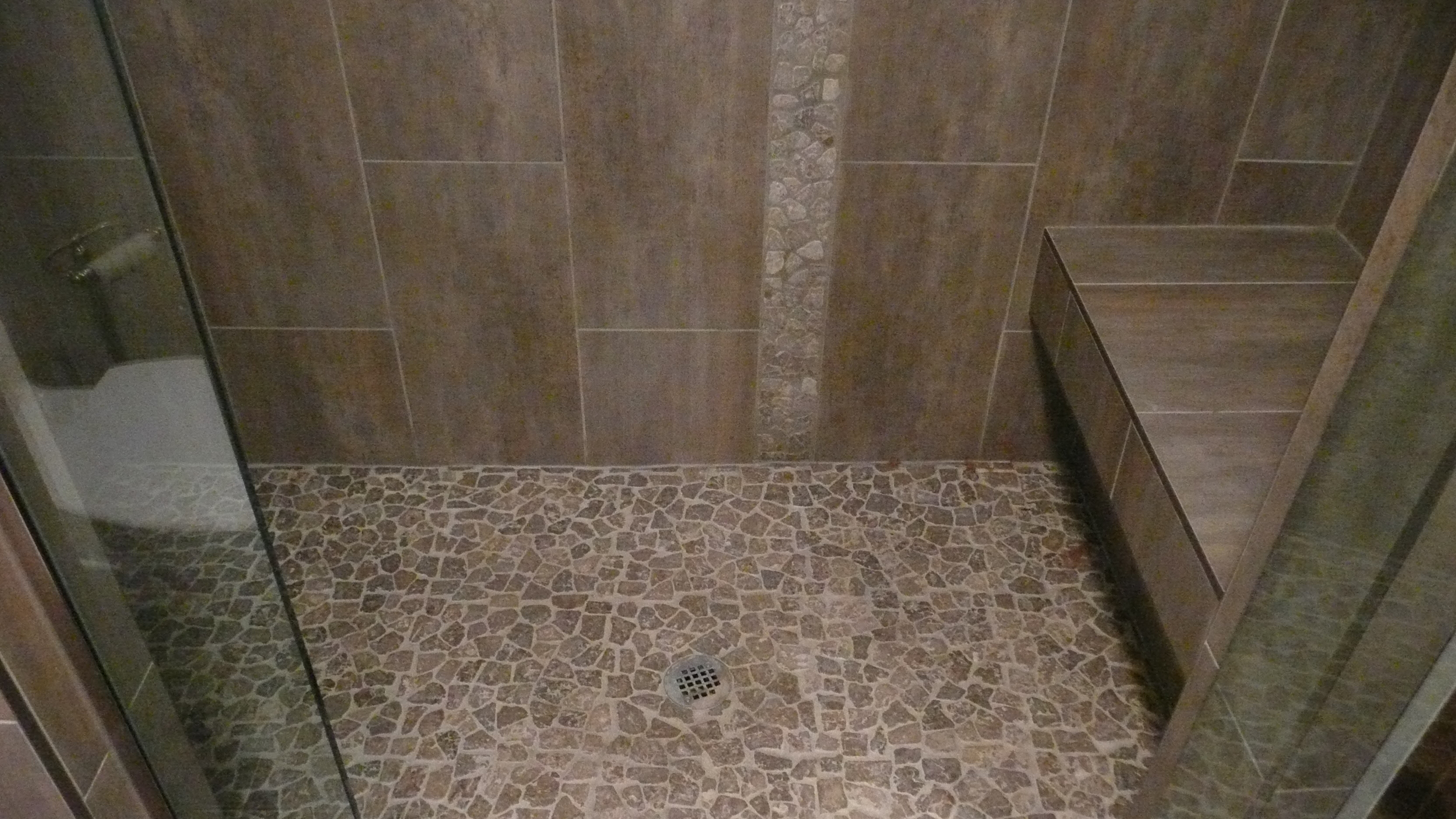 Porcelain and pebble custom shower with floating bench.