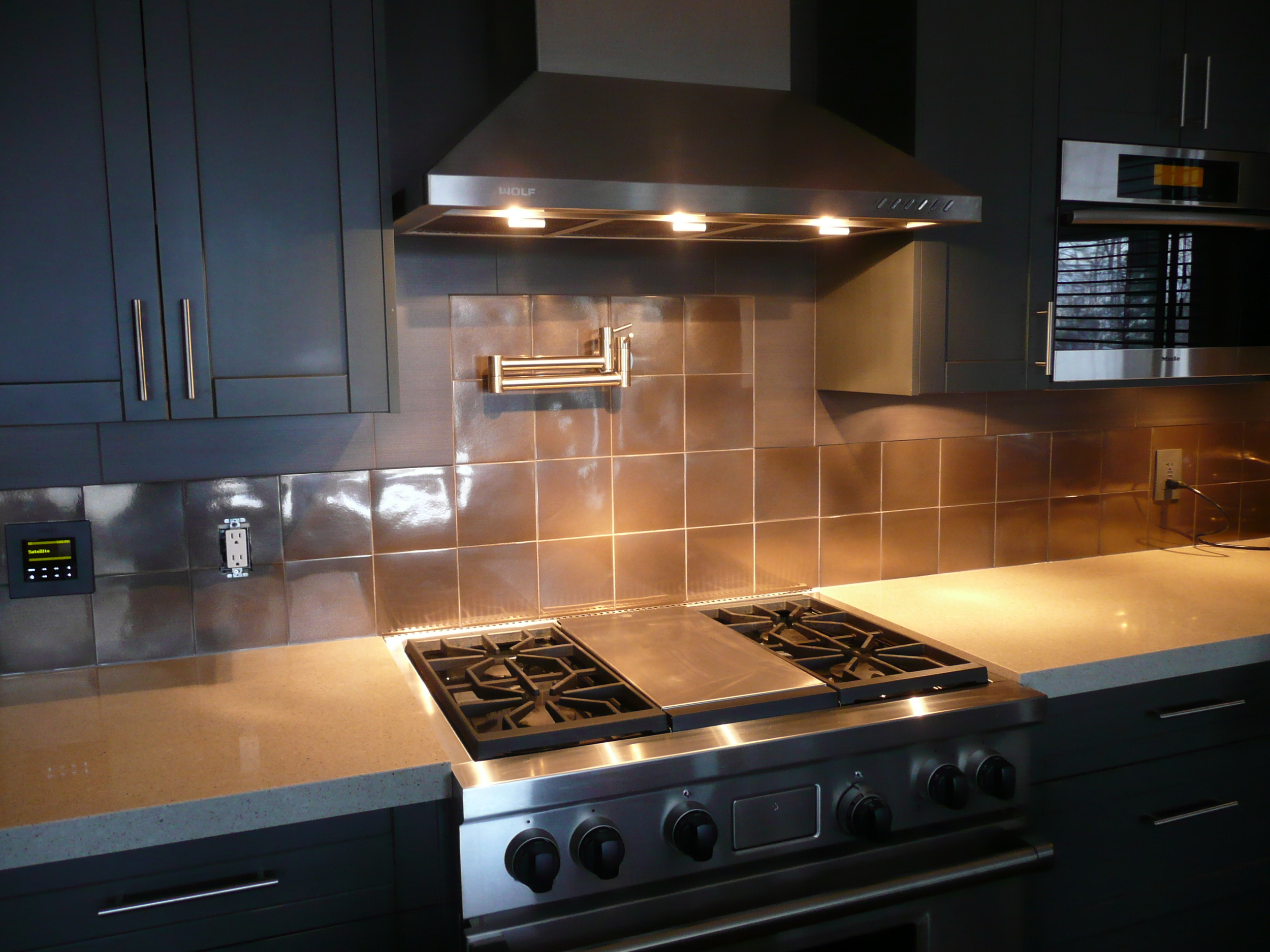 Stainless steel range and hood, steel look tile and porcelain backsplash.