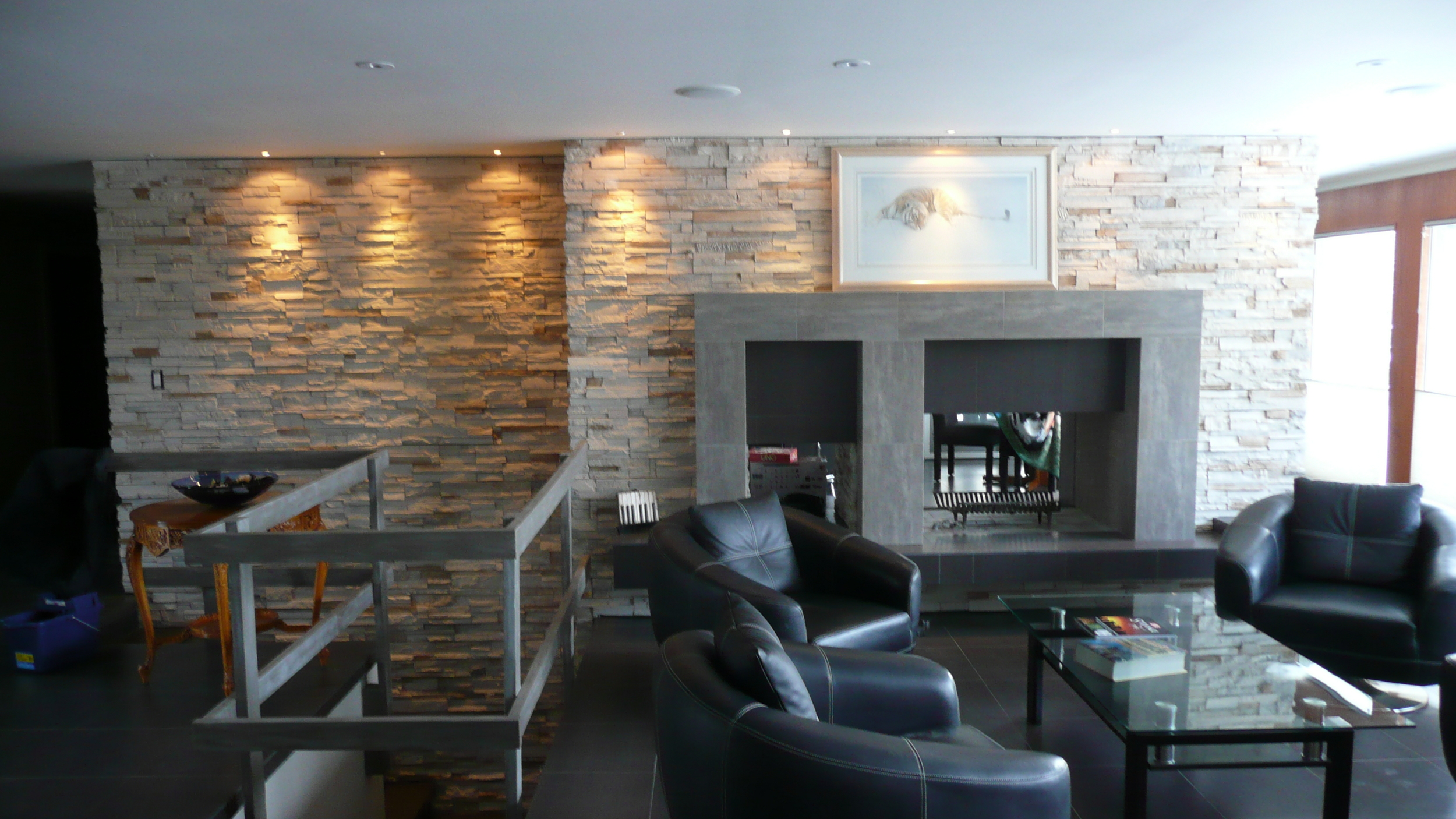 Custom manufactured stone and porcelain fireplace and feature wall, floating hearth.