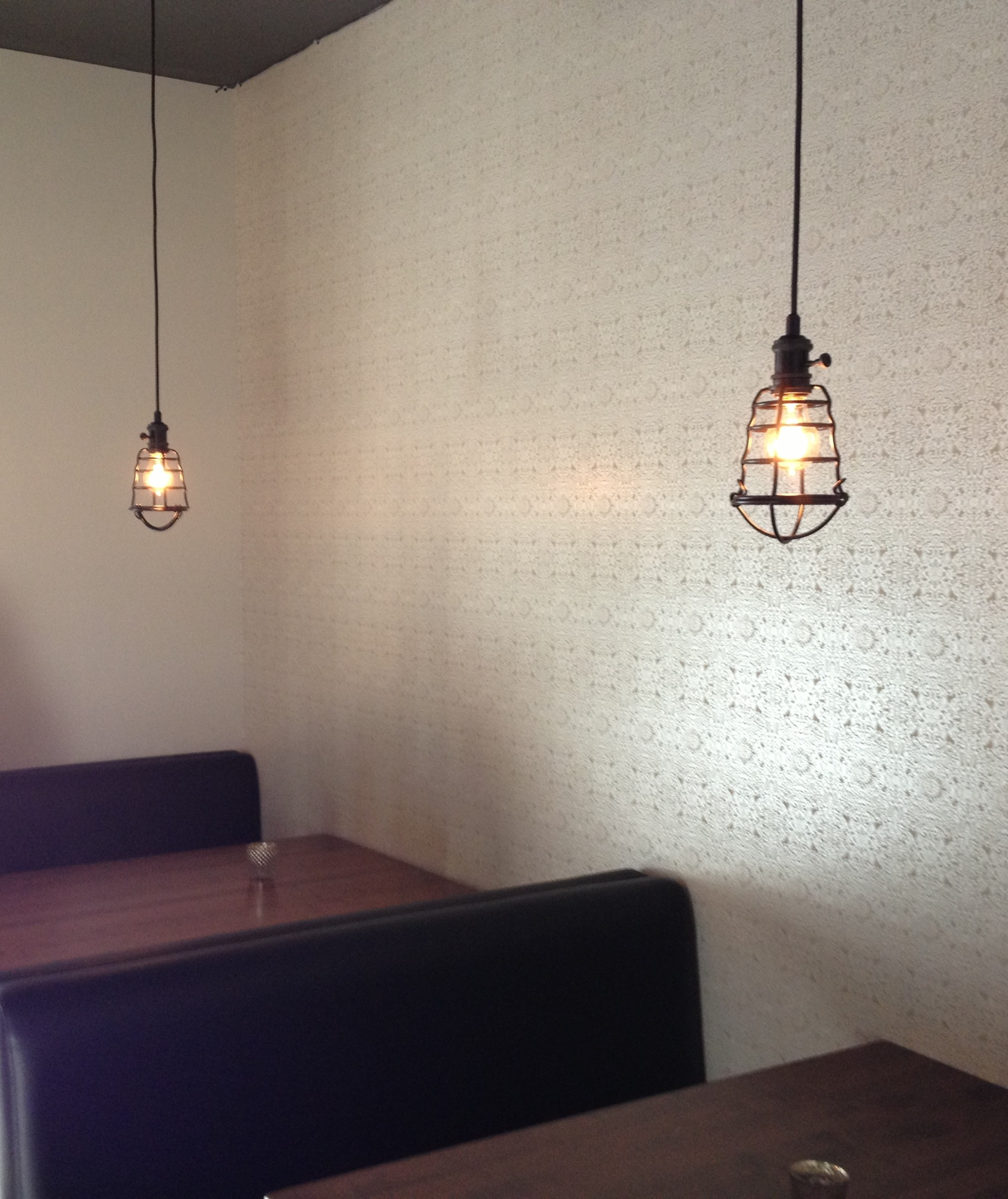 Moroccan wallpaper, industrial pendant lights, old style family booth seating.