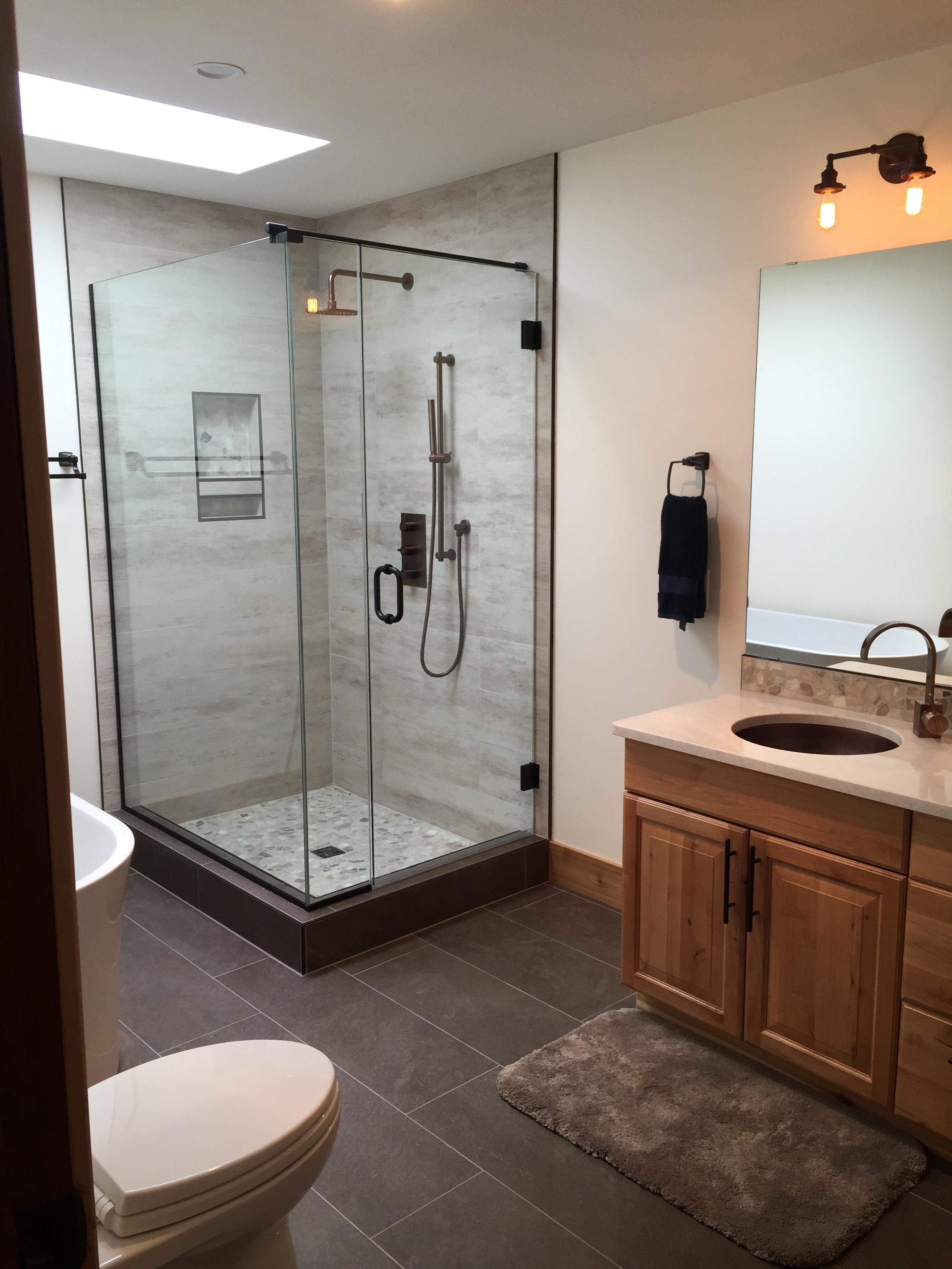 Custom shower, pebble shower floor and backsplash, large format porcelain tile, antique bronze fixtures.