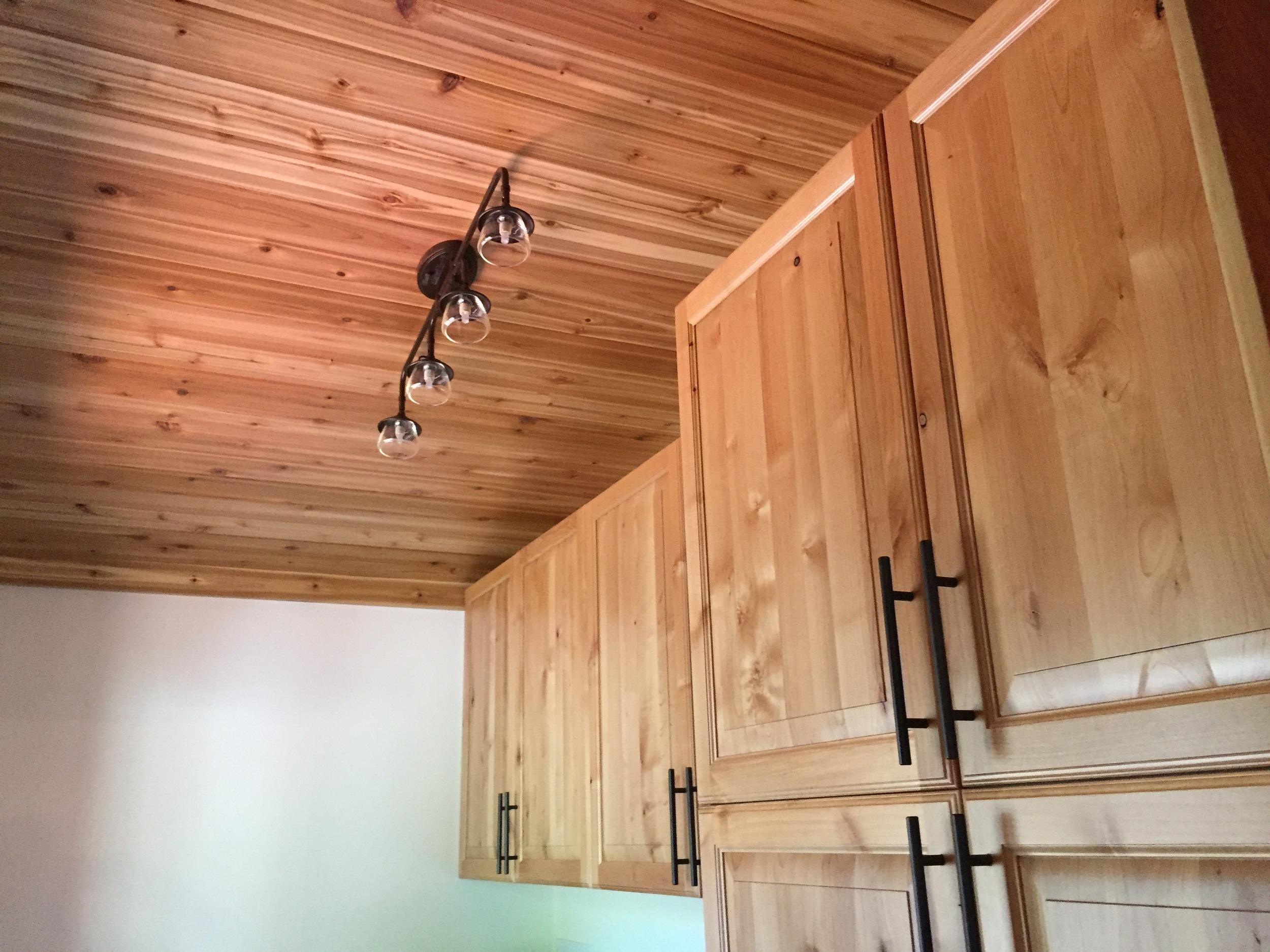 Cedar ceiling, vintage inspired lighting, hickory cabinets.