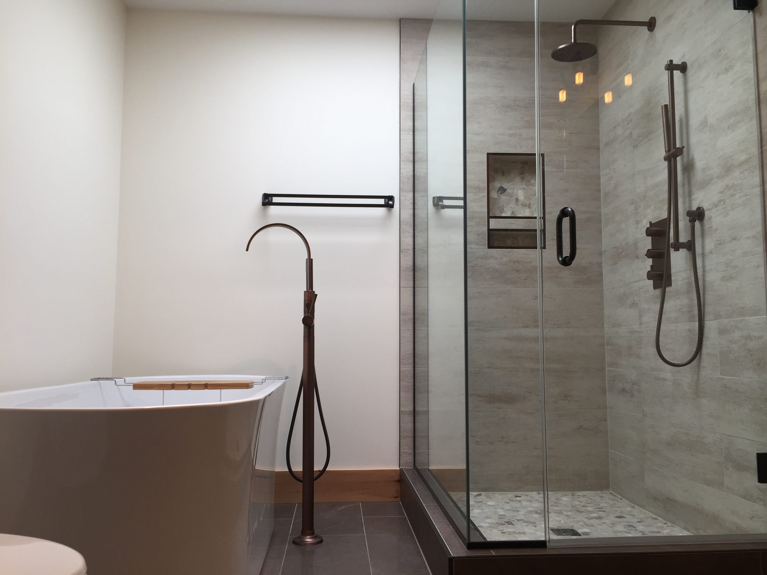 Freestanding bathtub and aged bronze tub filler, custom shower, pebble and porcelain.
