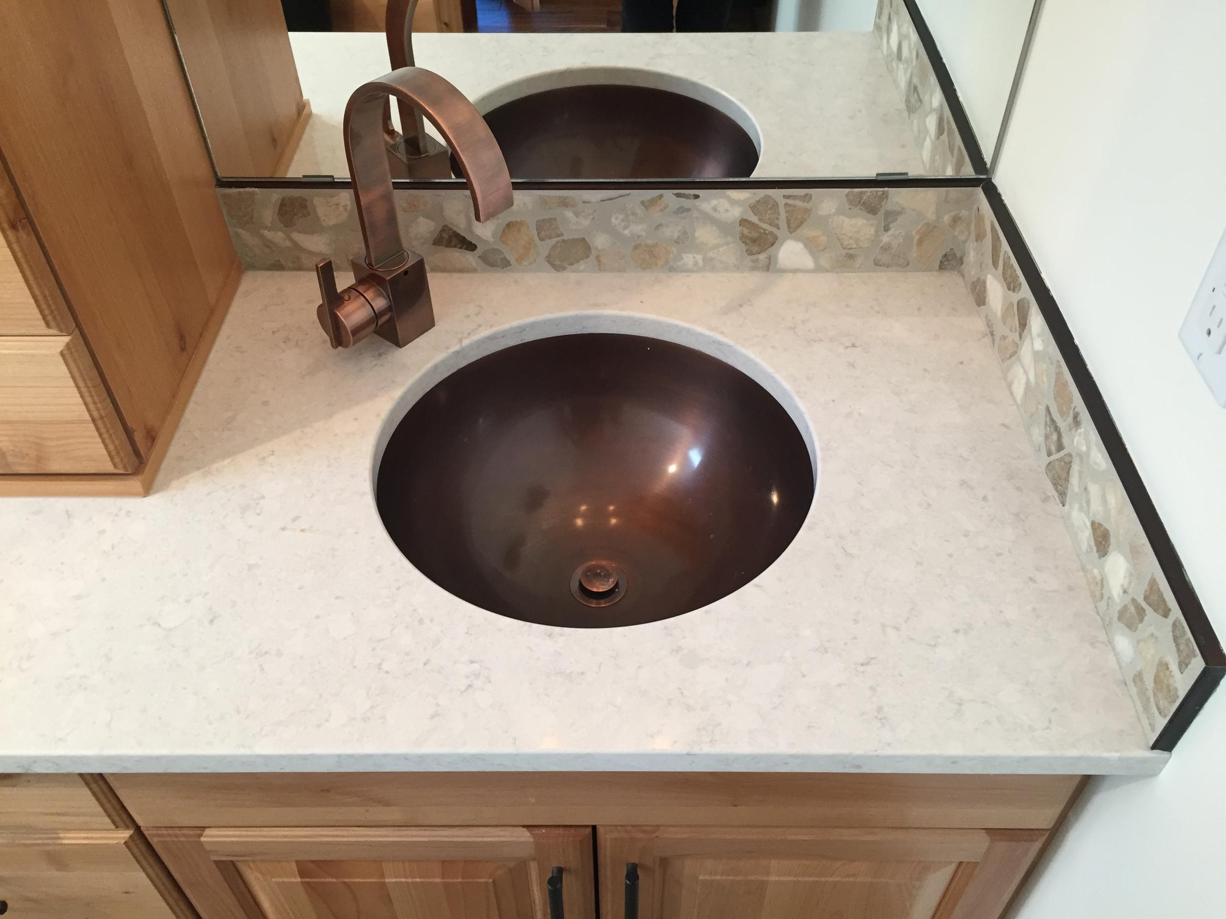 Antique copper sink, pebble backsplash, antique bronze faucet.