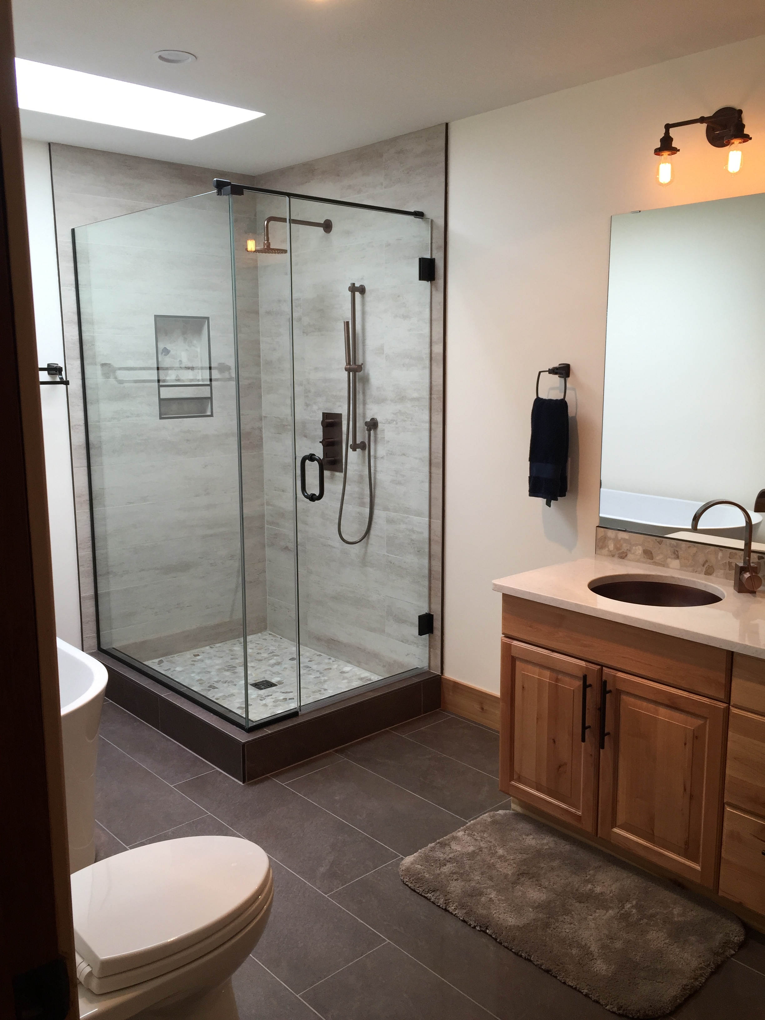 Custom shower and cabinetry, porcelain, pebbles and aged bronze fixtures.