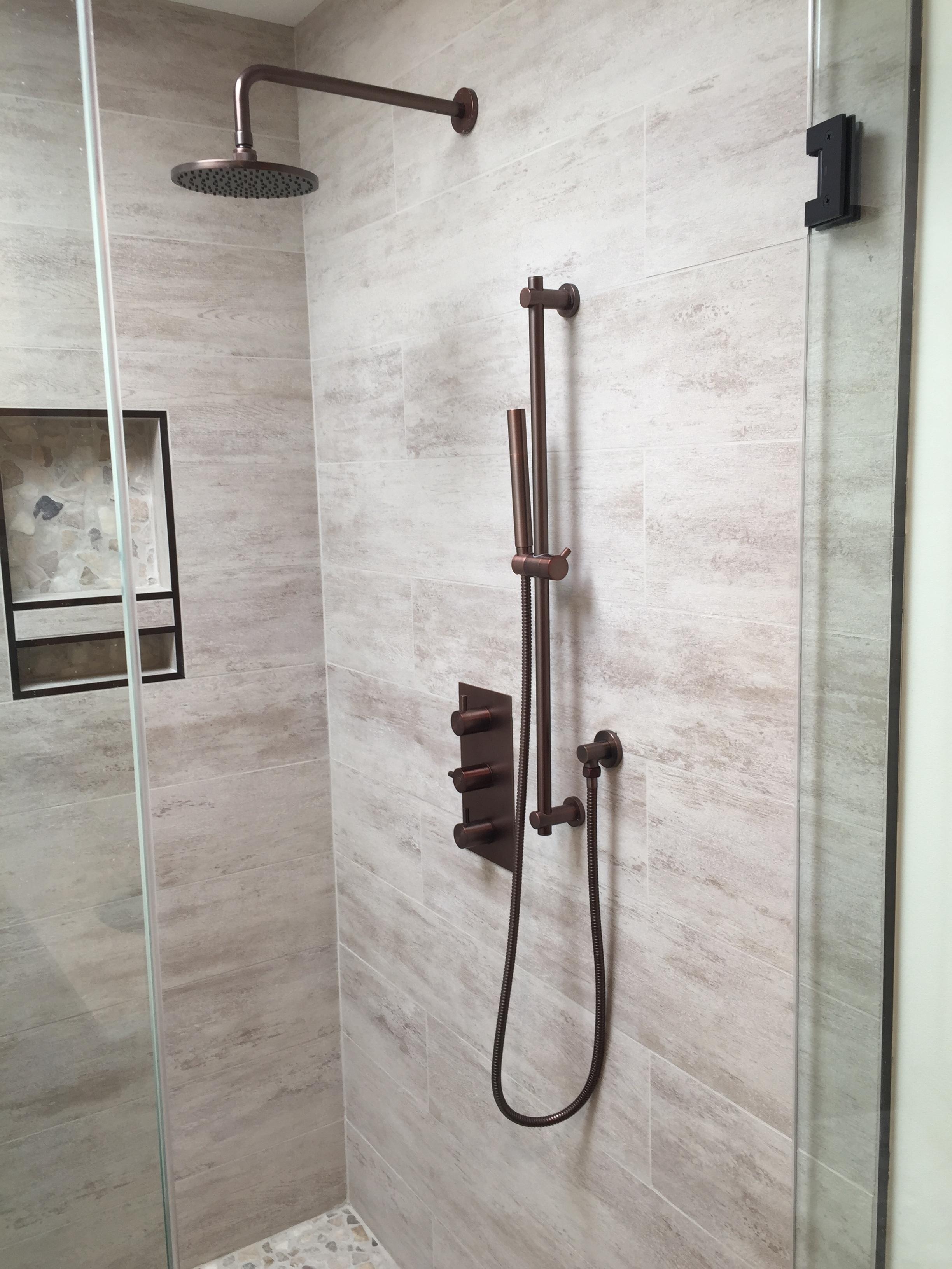 Custom shower, porcelain tile, pebble floor, recessed shower shelves, antique bronze fixtures.