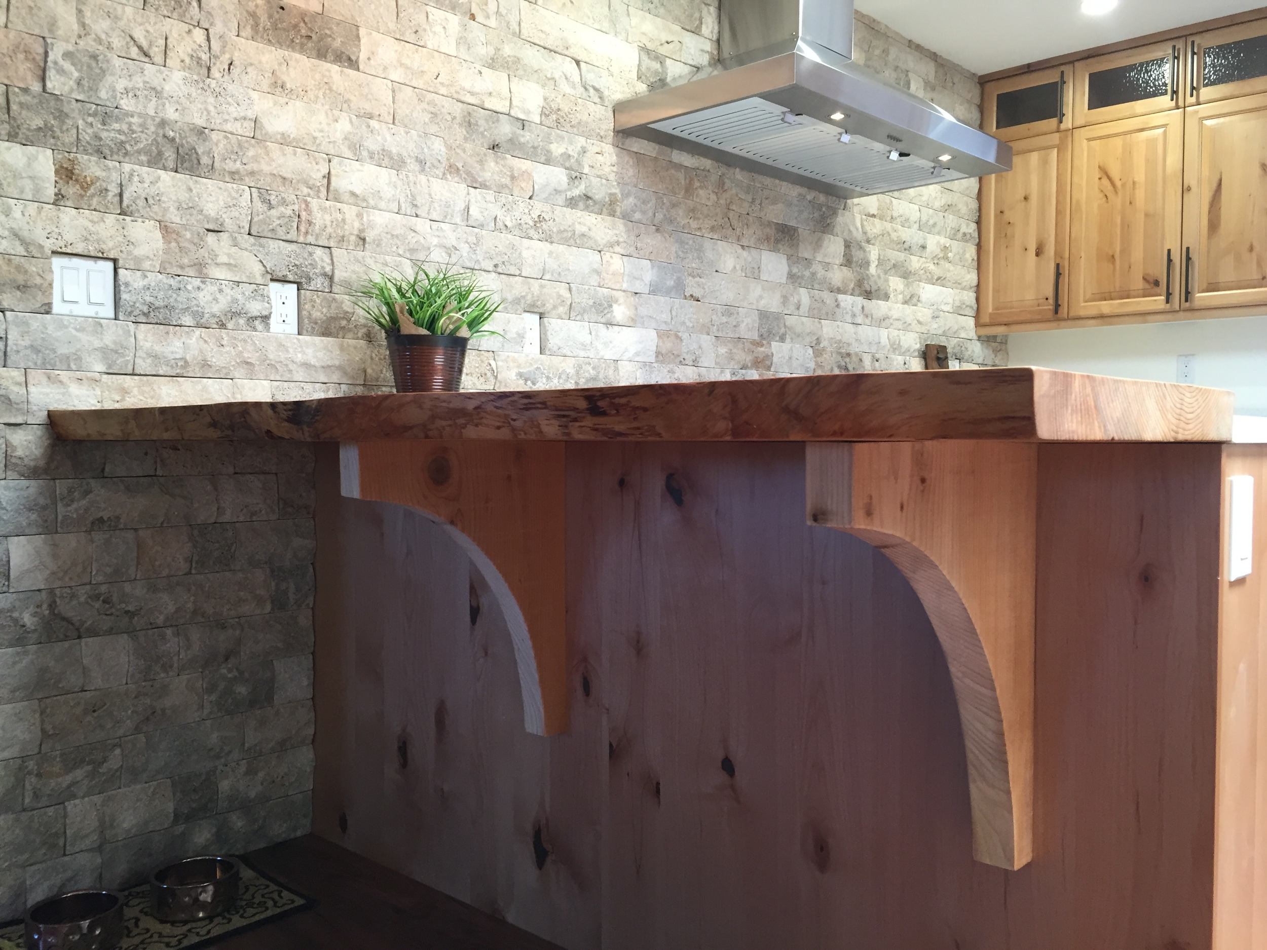 Live edge eating bar, hickory cabinets, rustic stone.