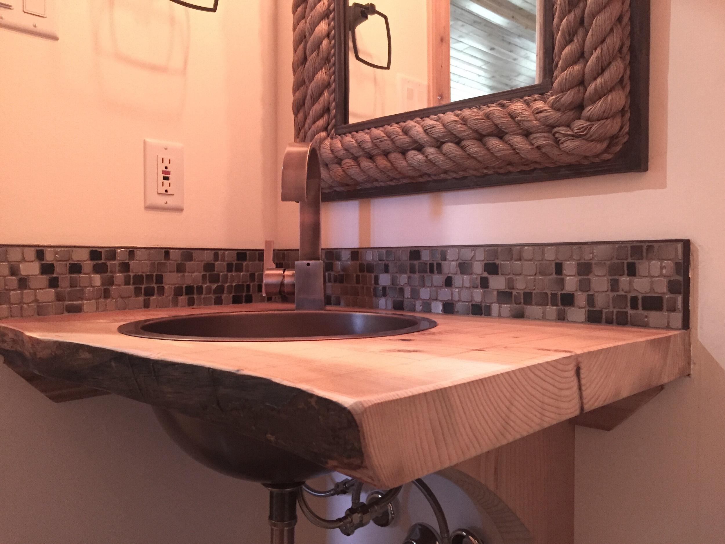 Rustic live edge countertop, antique copper sink and faucet, glass backsplash.